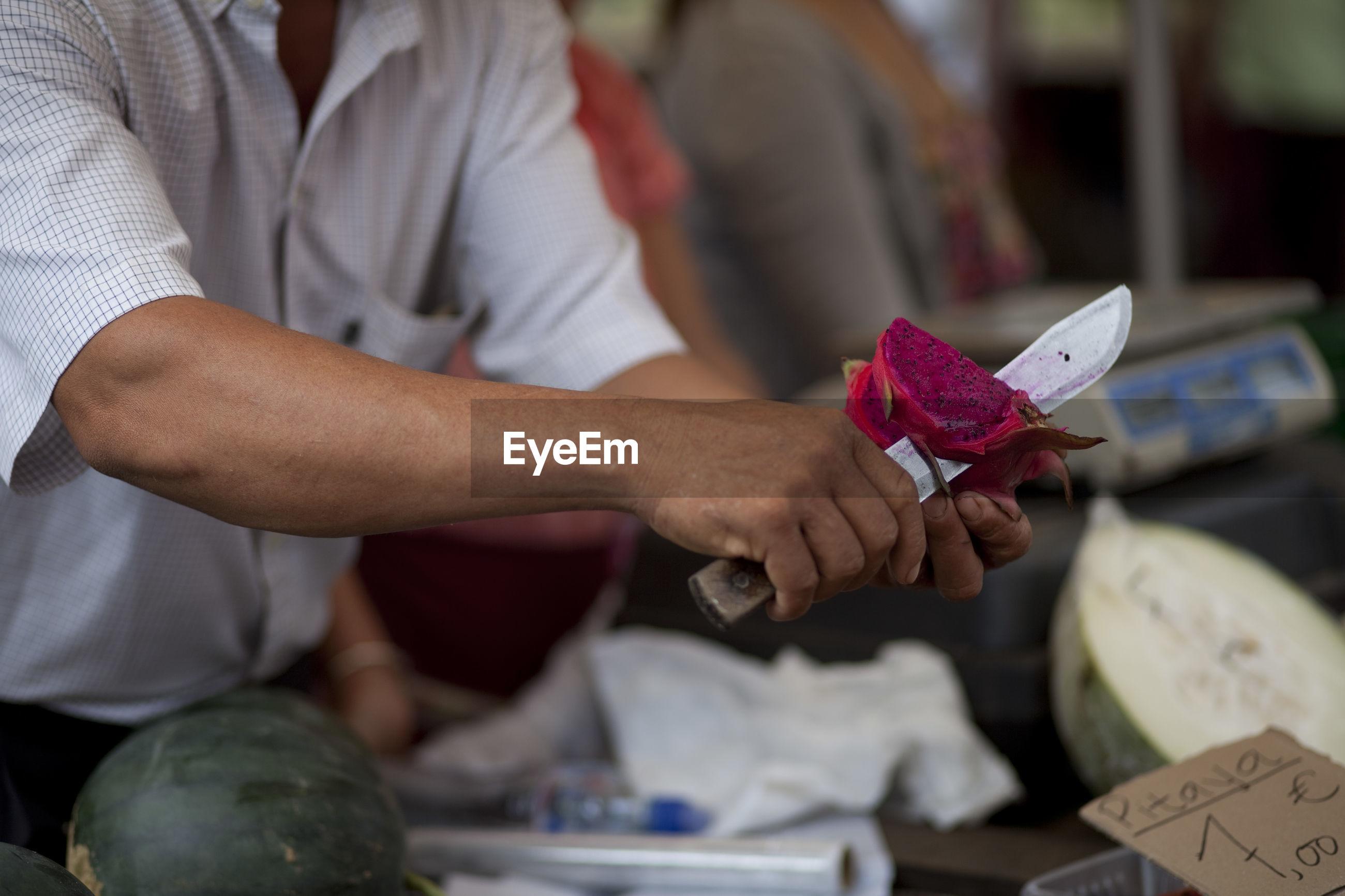 Midsection of market vendor cutting pitaya