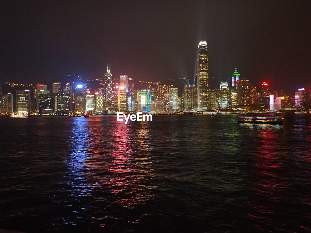 building exterior, architecture, skyscraper, illuminated, tall - high, night, built structure, city, urban skyline, cityscape, tower, travel destinations, modern, financial district, water, outdoors, waterfront, river, downtown district, no people, sky