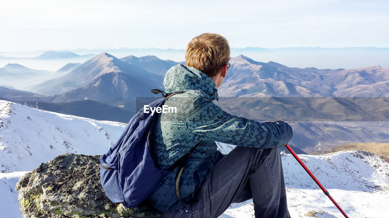 Rear View Of Man Sitting On Rock At Mountain