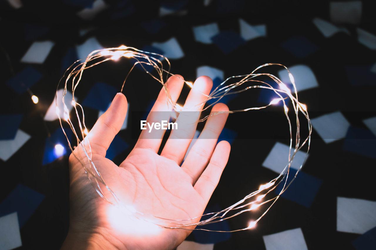Cropped hand holding heart shape illuminated string light