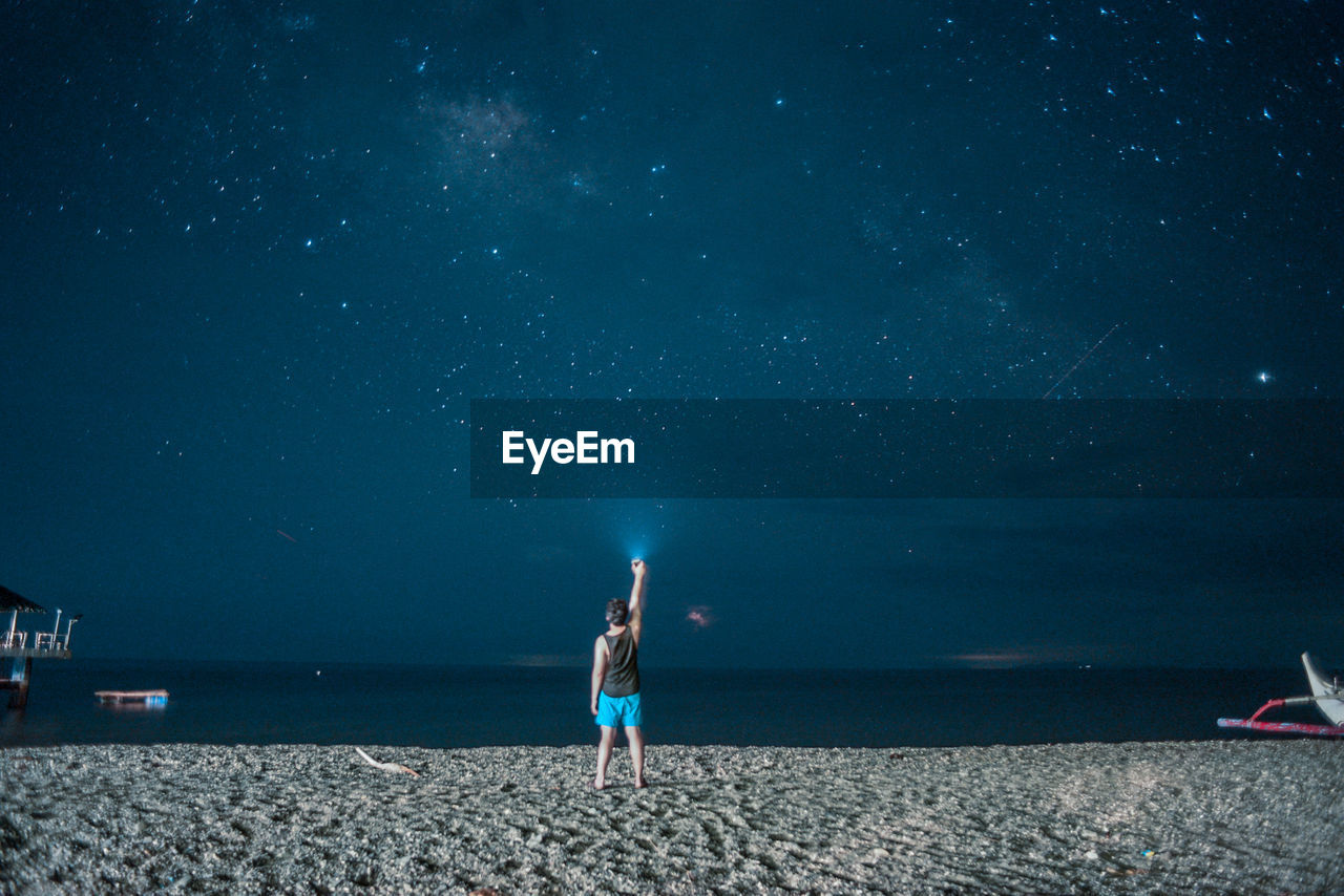 Rear View Of Boy Standing On Beach Against Sky At Night