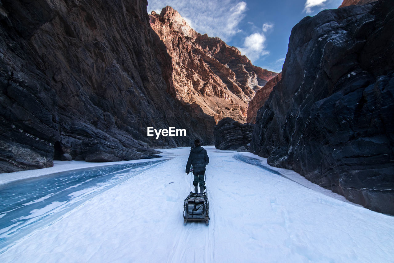 Rear view of person walking on snow covered mountain