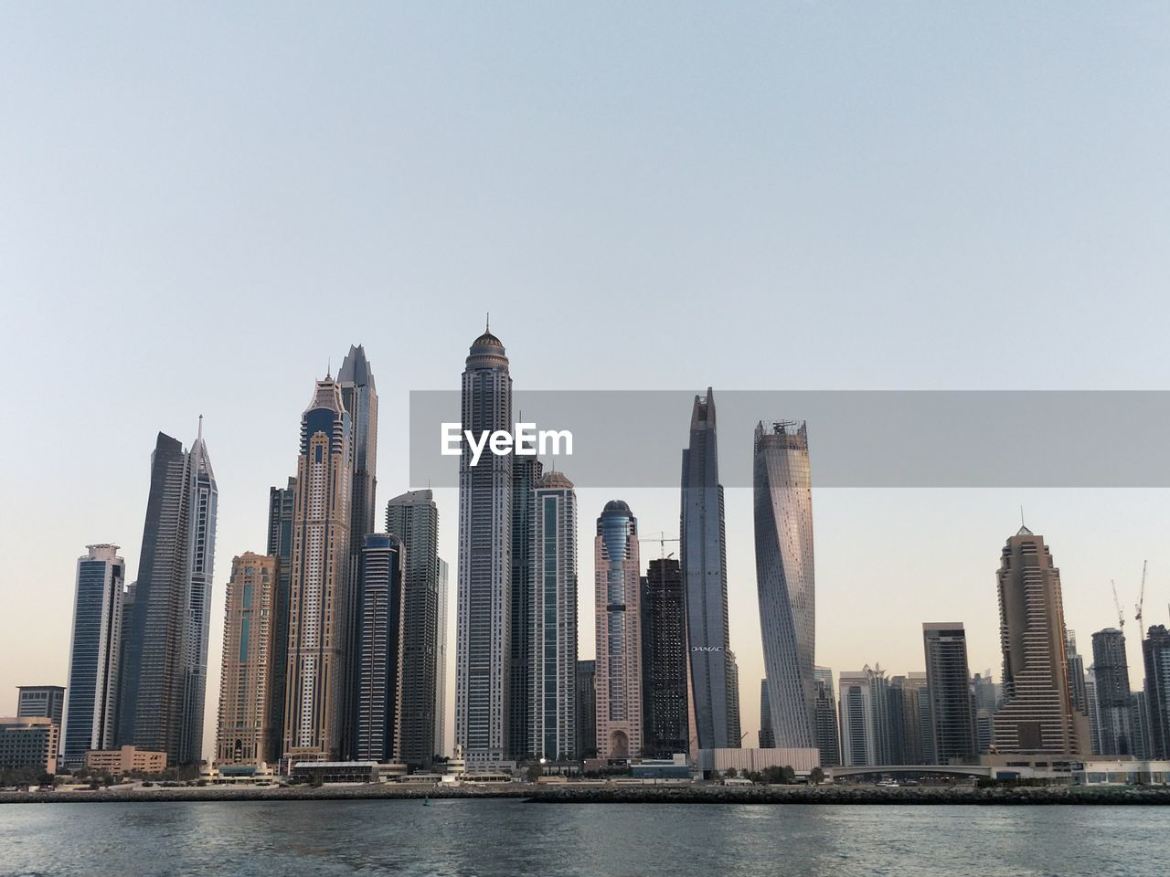skyscraper, architecture, tall - high, built structure, building exterior, city, urban skyline, tower, clear sky, modern, waterfront, financial district, travel destinations, water, cityscape, tourism, downtown district, sky, river, outdoors, day, no people