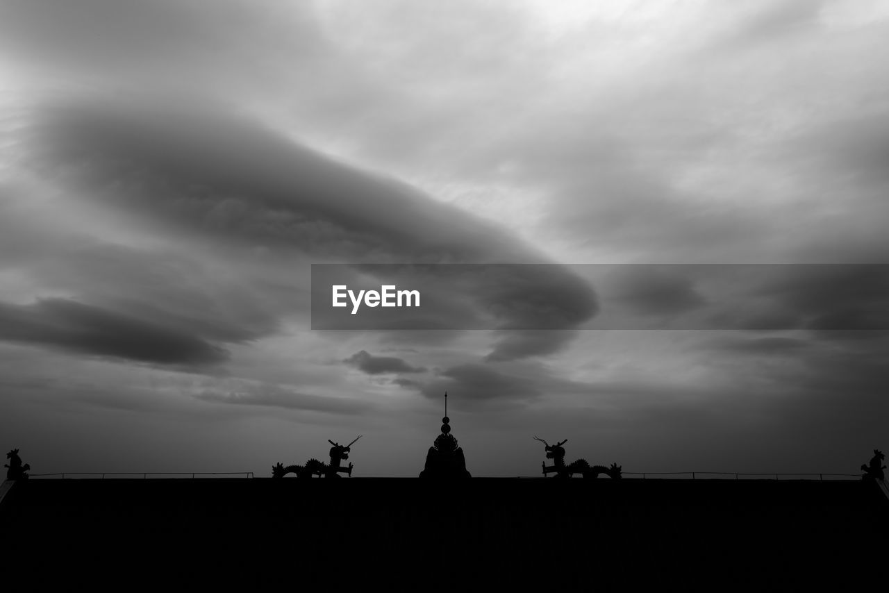 cloud - sky, silhouette, sky, statue, weather, sculpture, nature, outdoors, history, sunset, no people, low angle view, travel destinations, built structure, landscape, storm cloud, day, beauty in nature, windmill, architecture, city