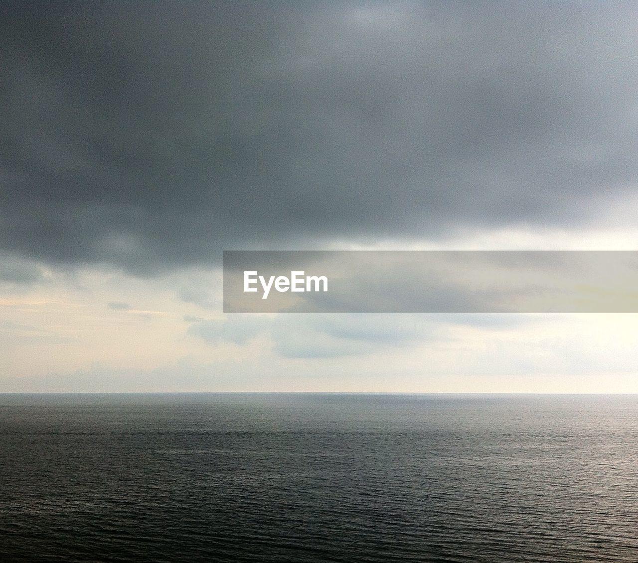 Calm sea against cloudy sky