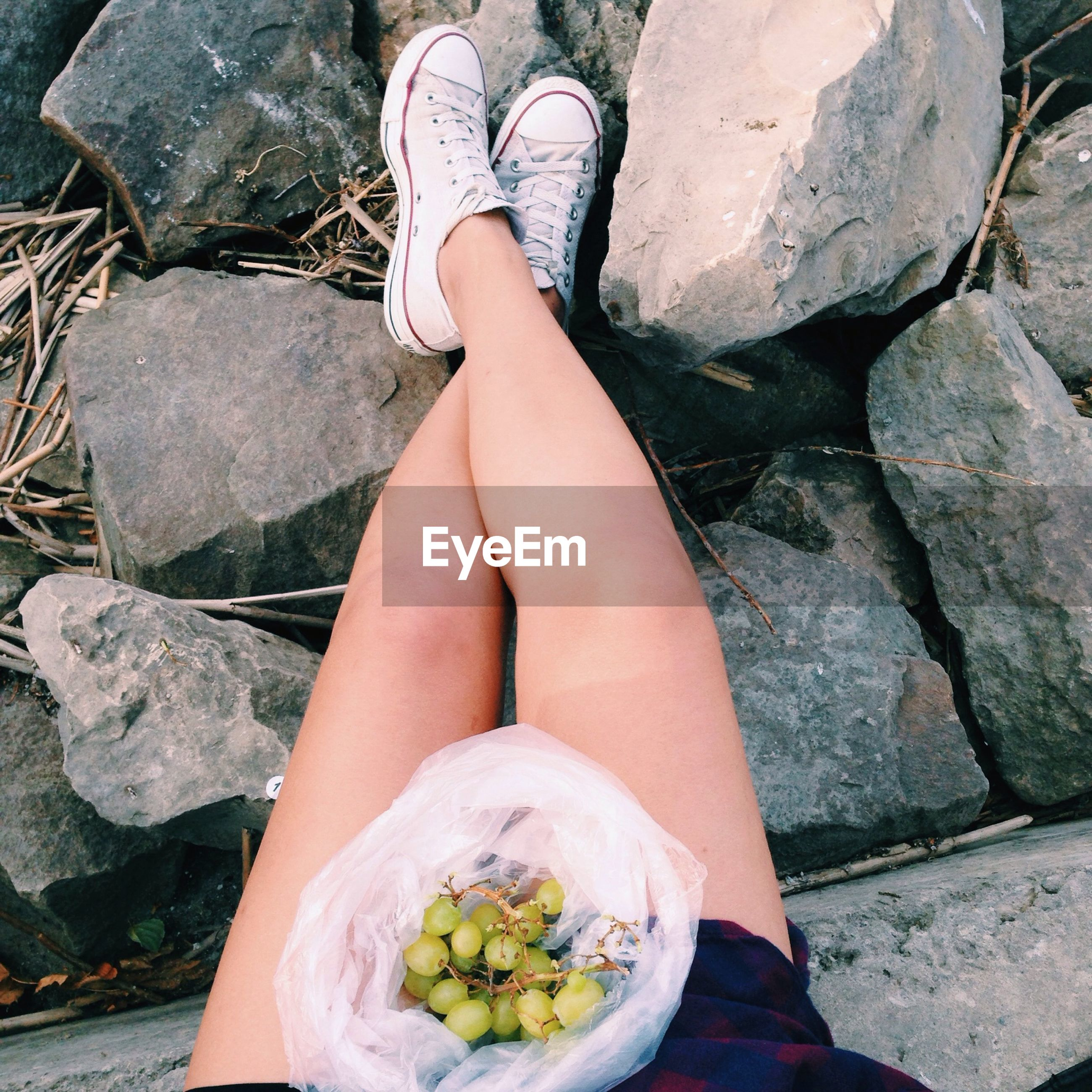 low section, lifestyles, person, leisure activity, standing, personal perspective, shoe, high angle view, outdoors, human foot, leaf, rock - object, holding, day, sitting, freshness