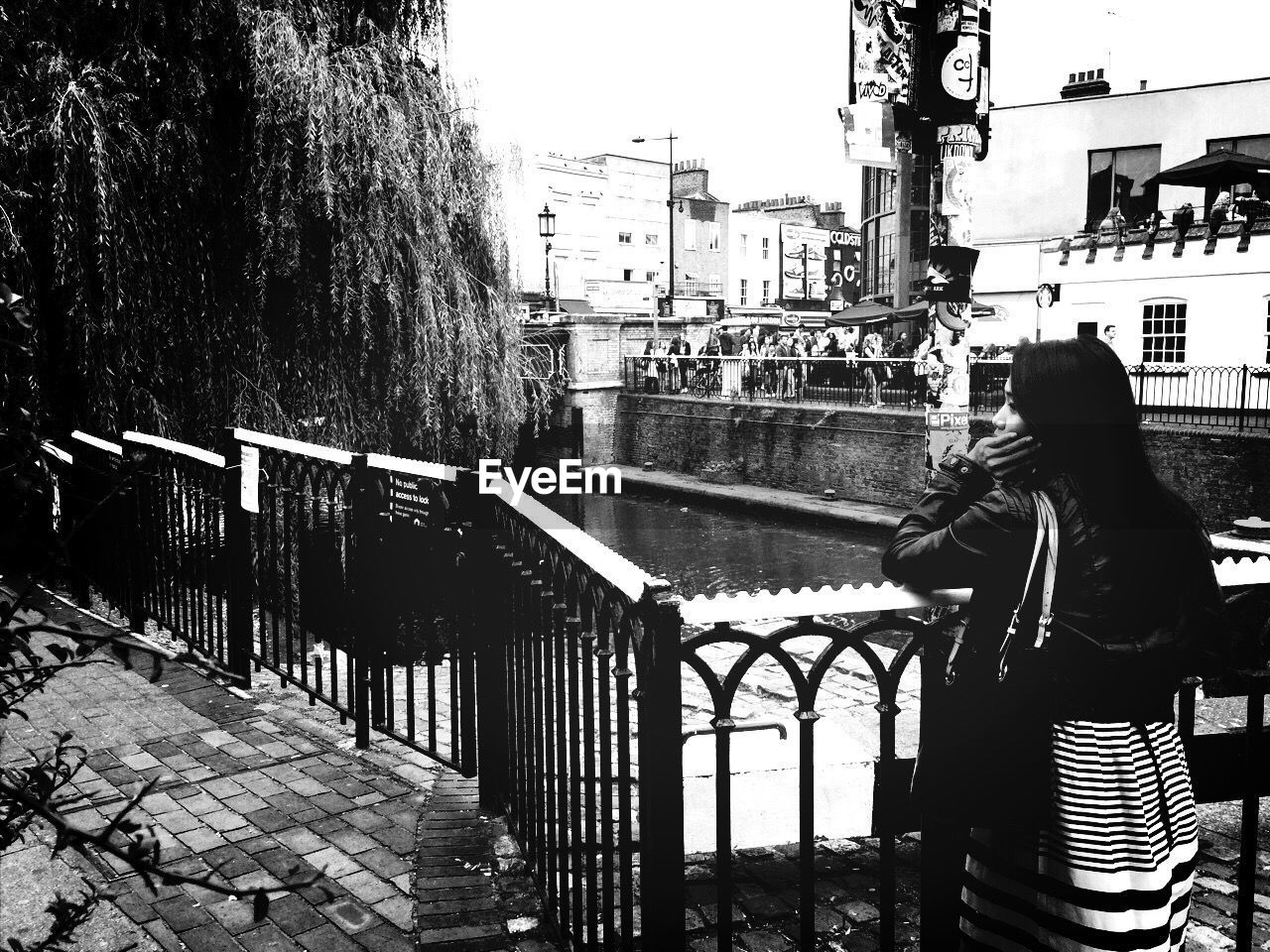 Rear View Of Woman Leaning Against Railing Beside Canal