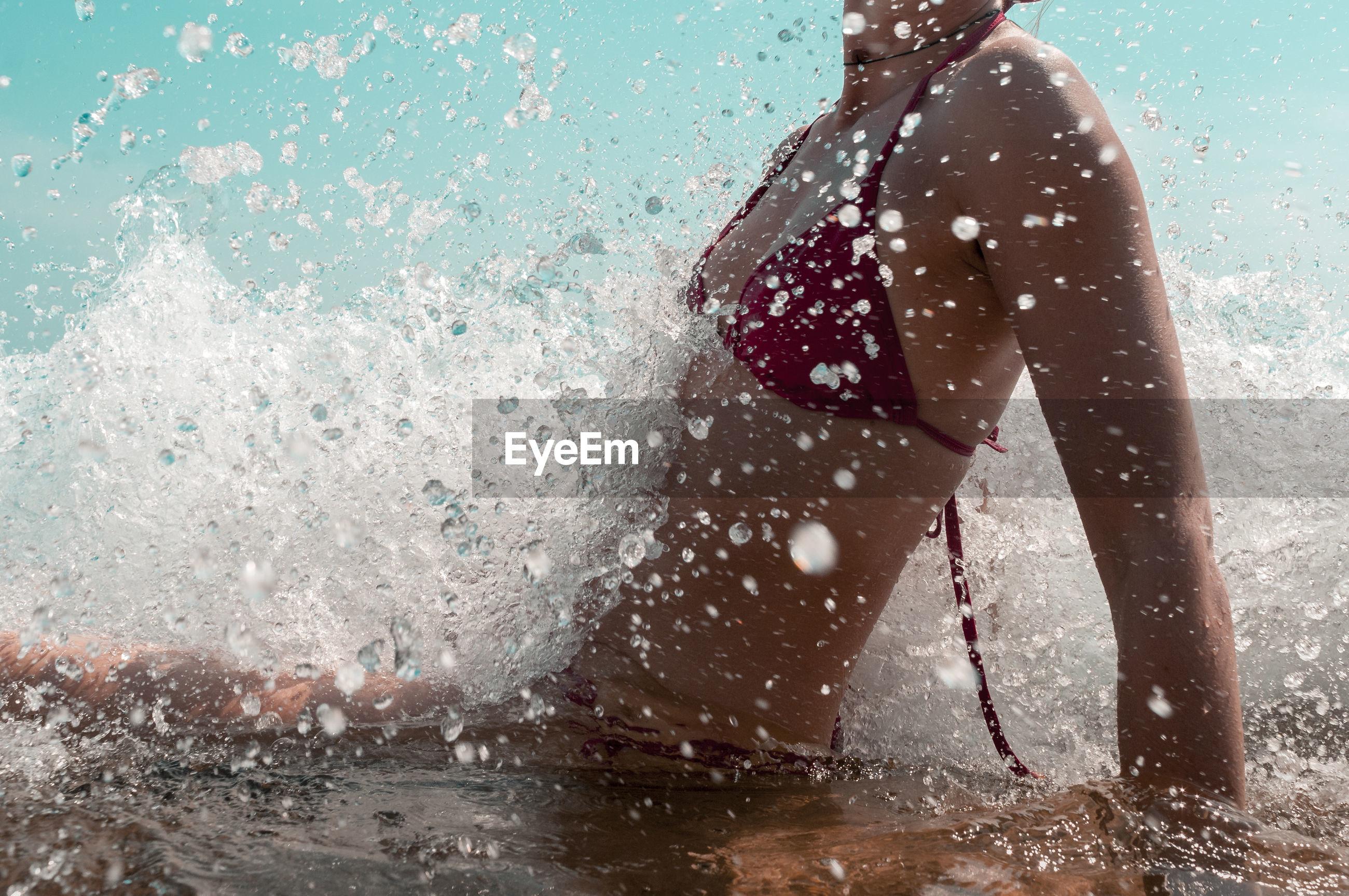 Midsection of young woman wearing bikini swimming in sea