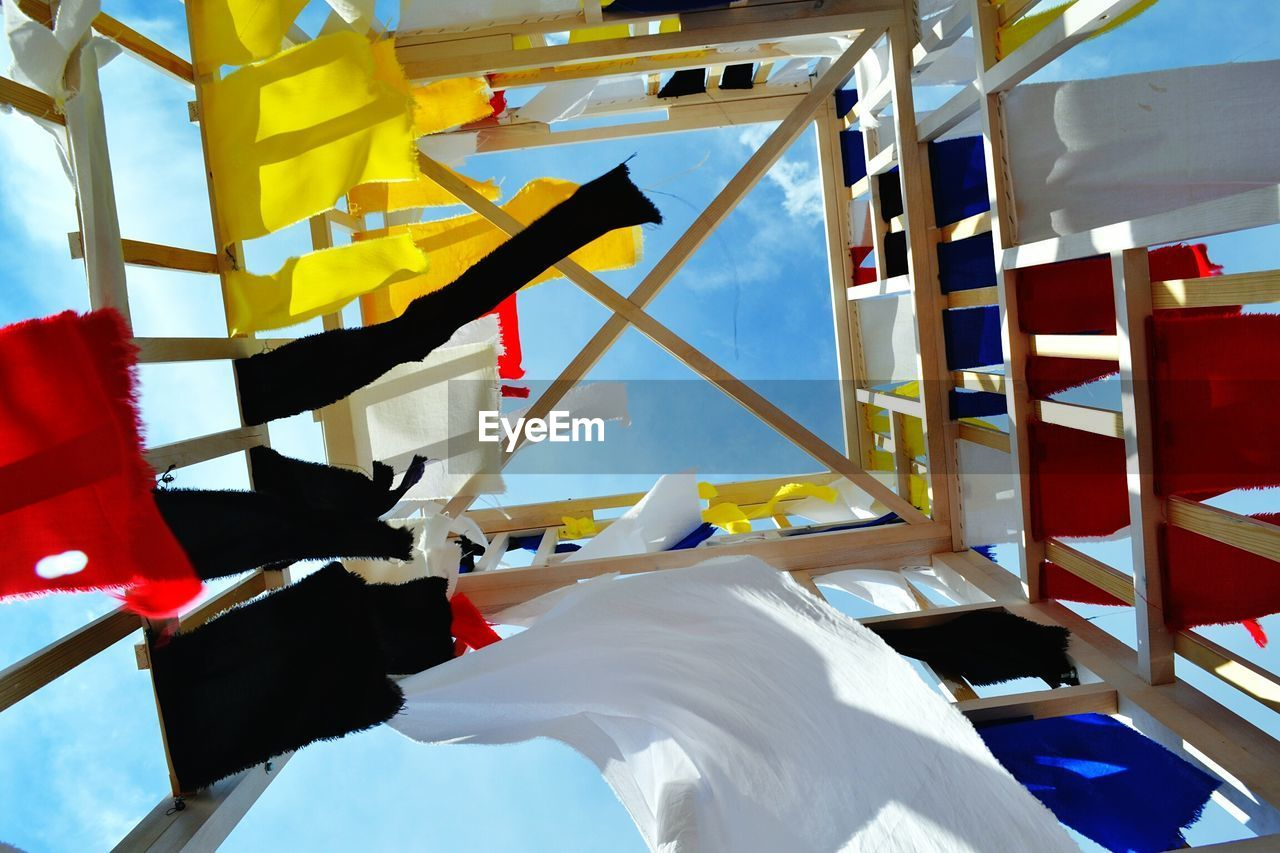 Directly Below Shot Of Multi Colored Fabrics Hanging On Wooden Structure