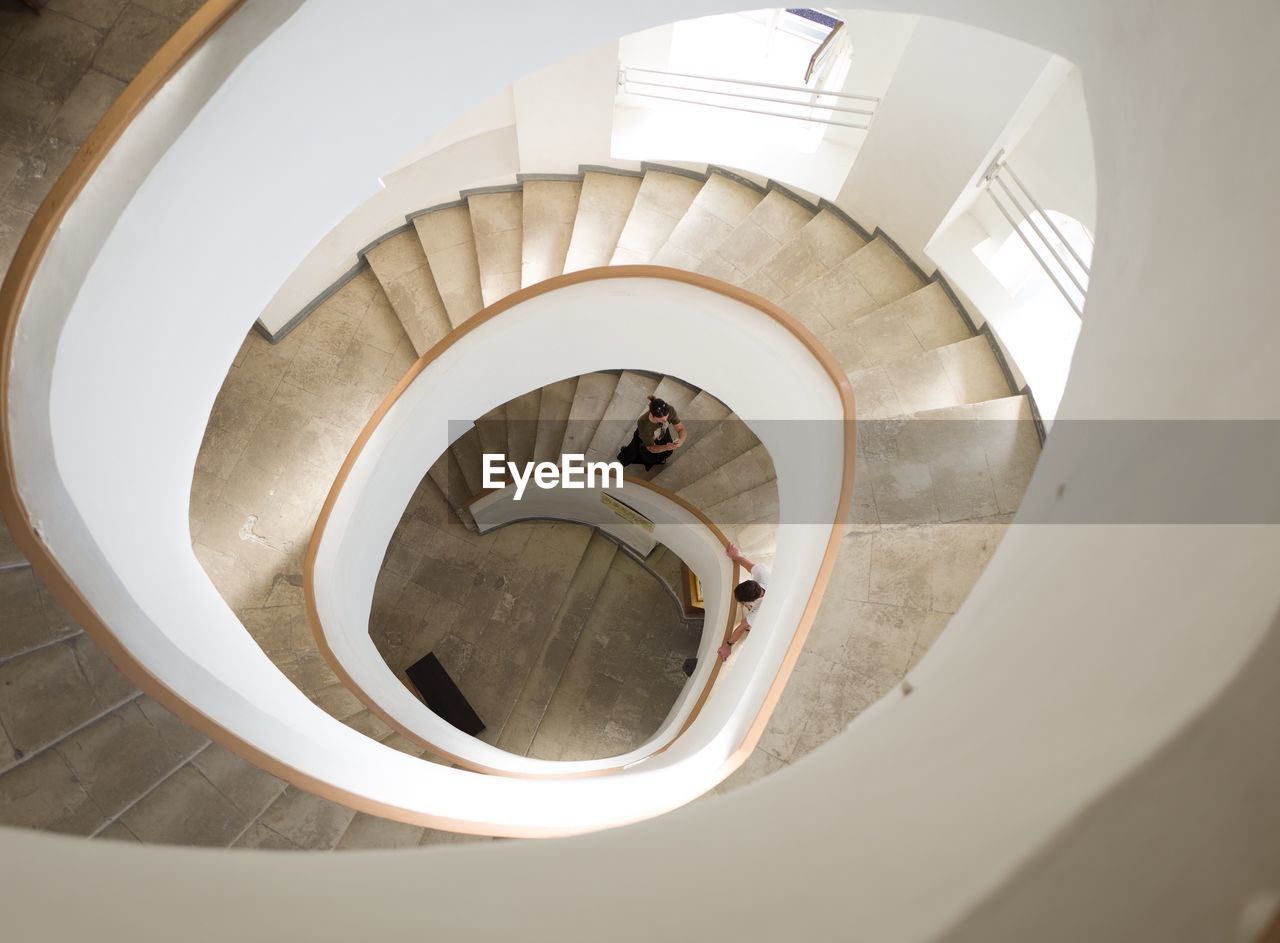 staircase, steps and staircases, spiral staircase, spiral, high angle view, architecture, built structure, indoors, railing, real people, one person, directly above, adult, design, women, lifestyles, moving down, day, men