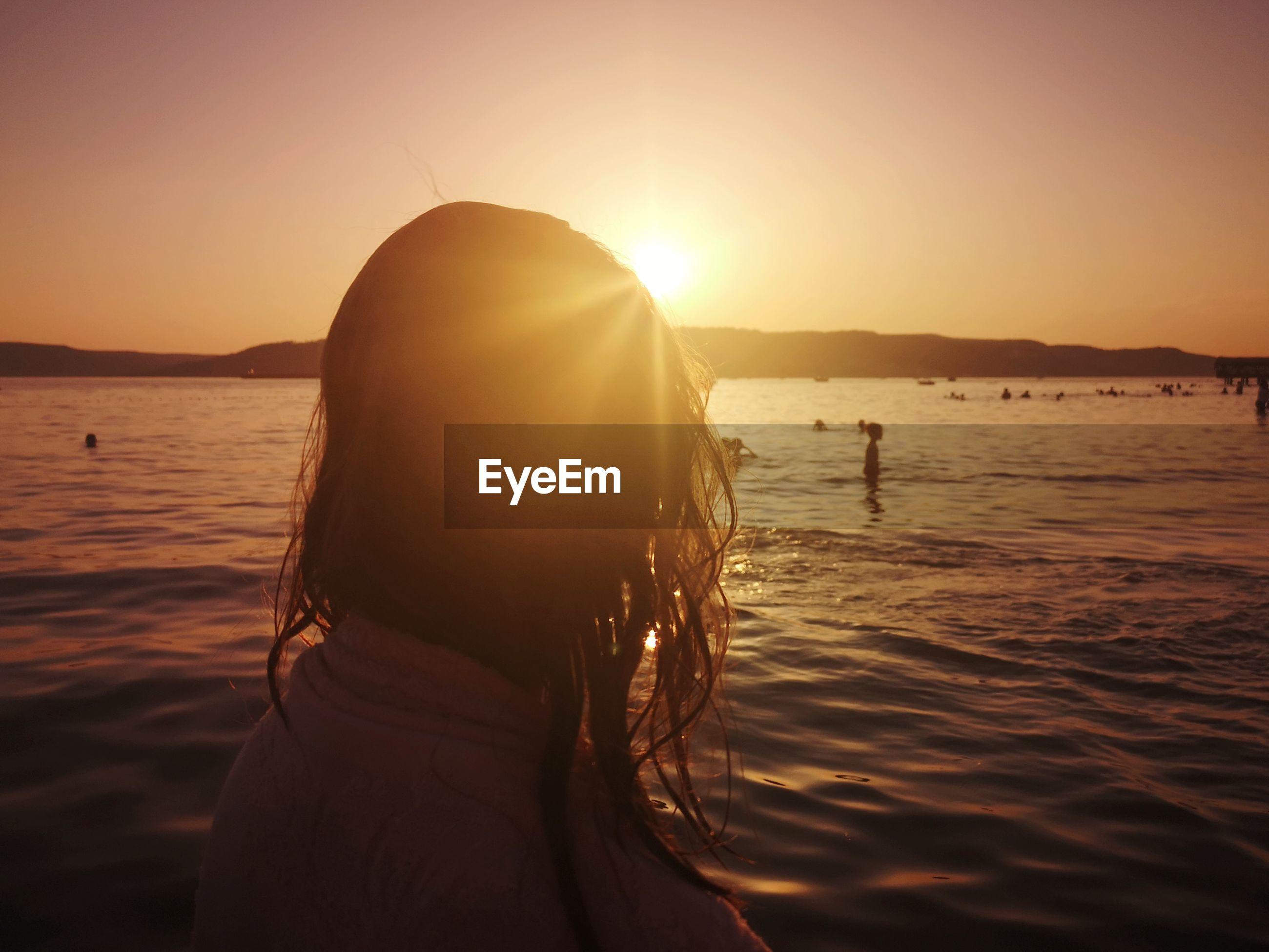 WOMAN ON BEACH AGAINST BRIGHT SUN