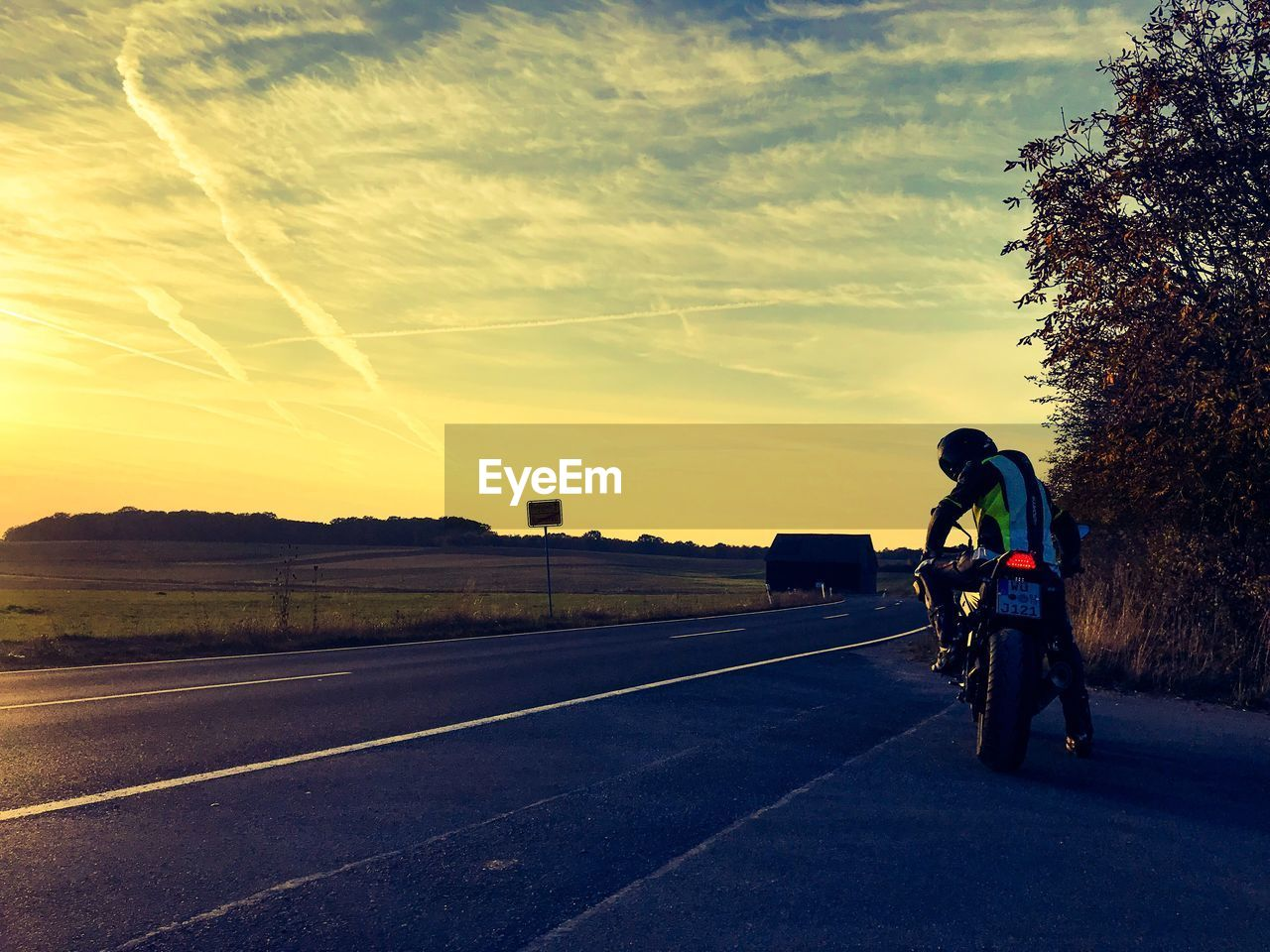 transportation, sky, one person, road, sunset, bicycle, full length, rear view, cloud - sky, nature, symbol, men, real people, mode of transportation, sign, road marking, land vehicle, tree, travel, outdoors, riding
