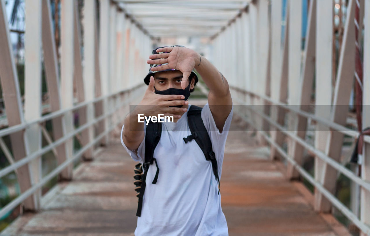 Young photography posing on footbridge while wearing a protective mask to prevent covid-19 infection