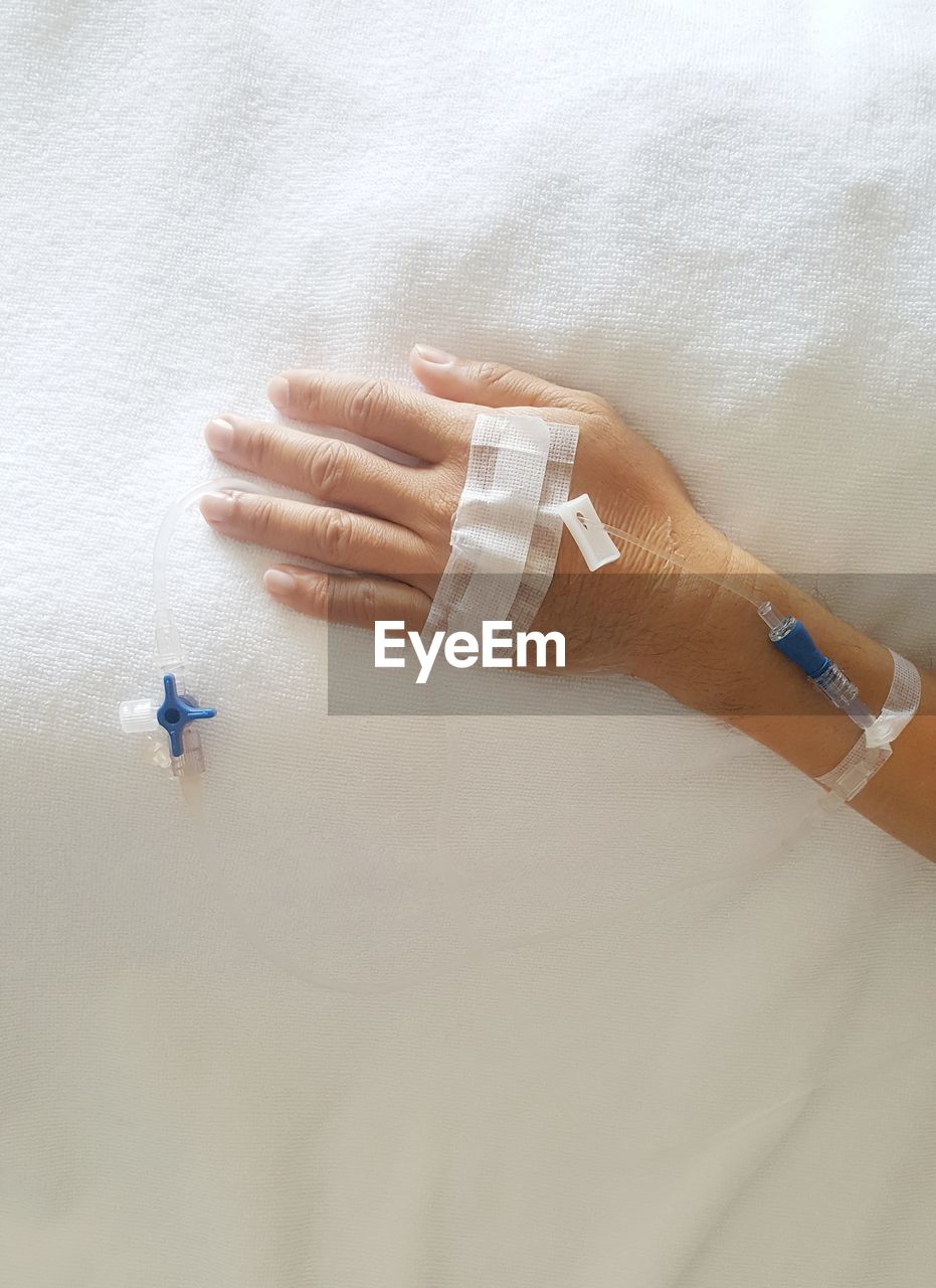 Close-Up Of Person Hand With Iv Drip On Bed