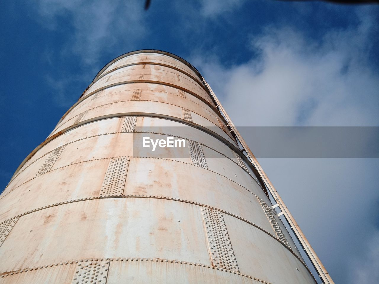Low angle view of storage tank against cloudy sky