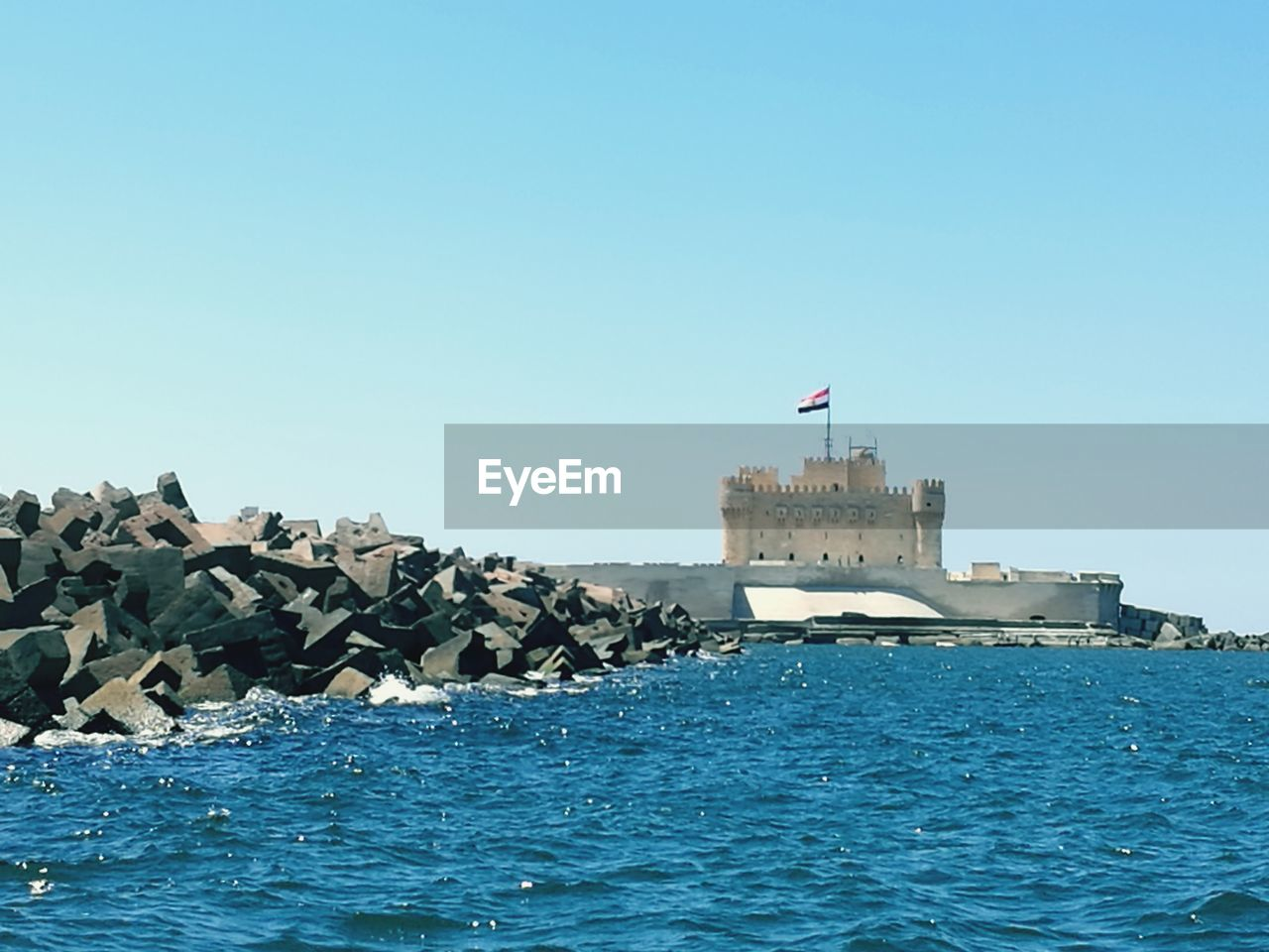 water, waterfront, flag, sky, built structure, architecture, building exterior, sea, clear sky, patriotism, day, nature, copy space, rock, outdoors, building, blue, solid, no people