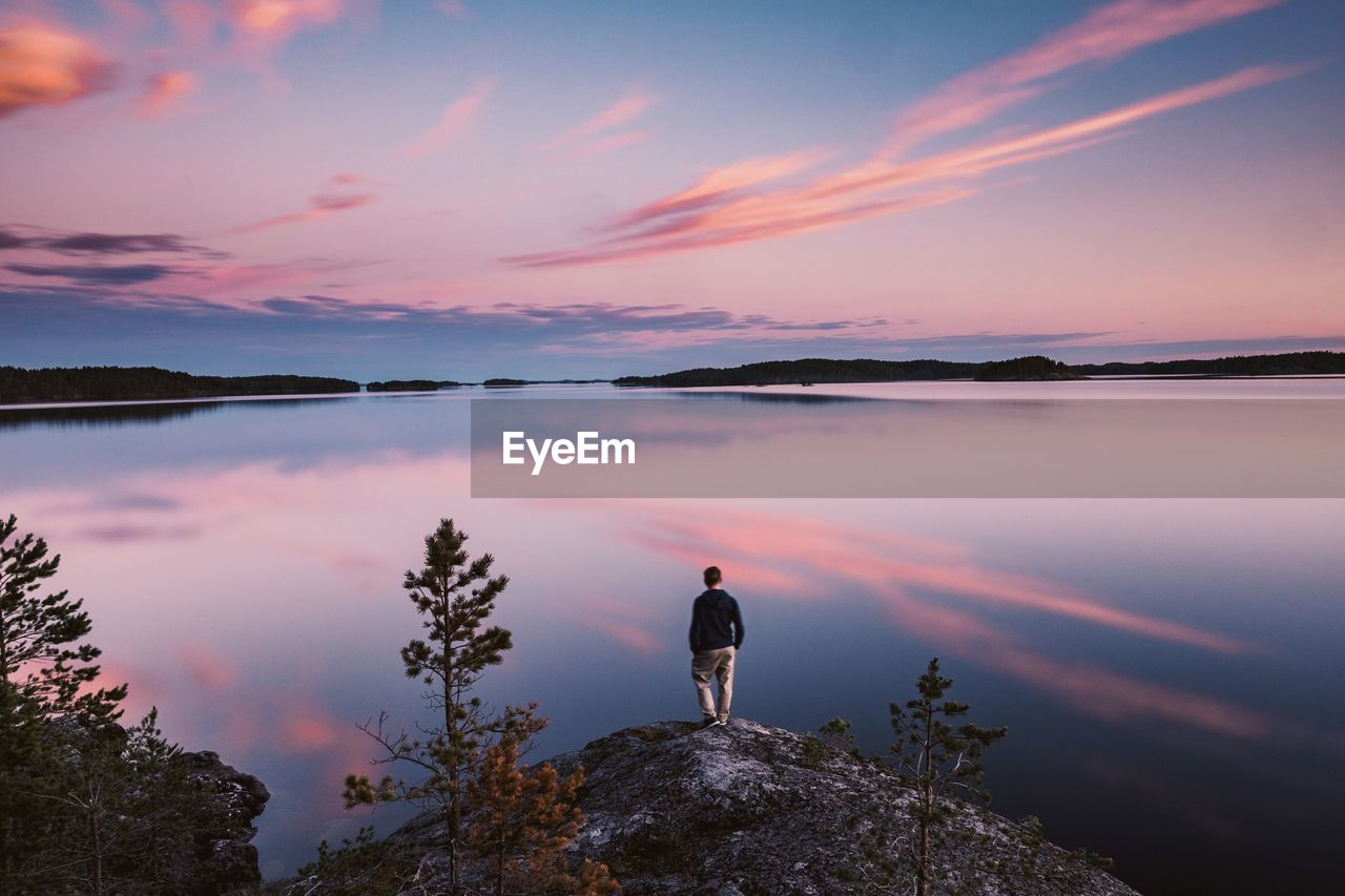 Man Standing On Rock By Lake Against Sky During Sunset