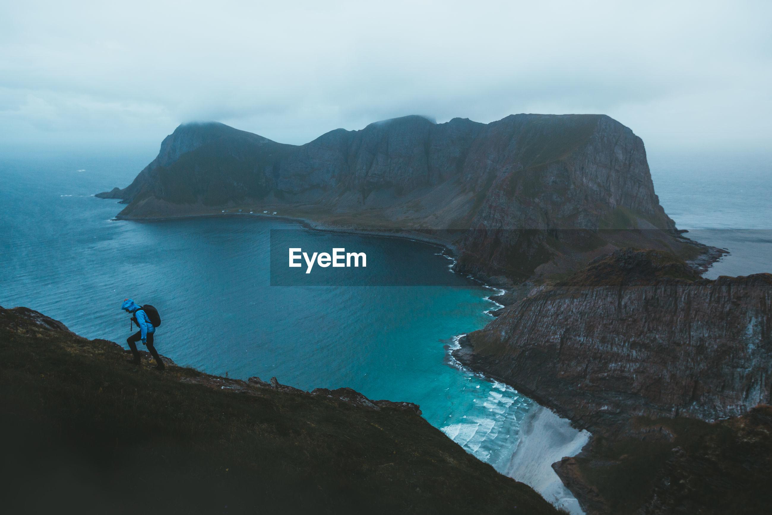 Man walking on mountain by sea against sky