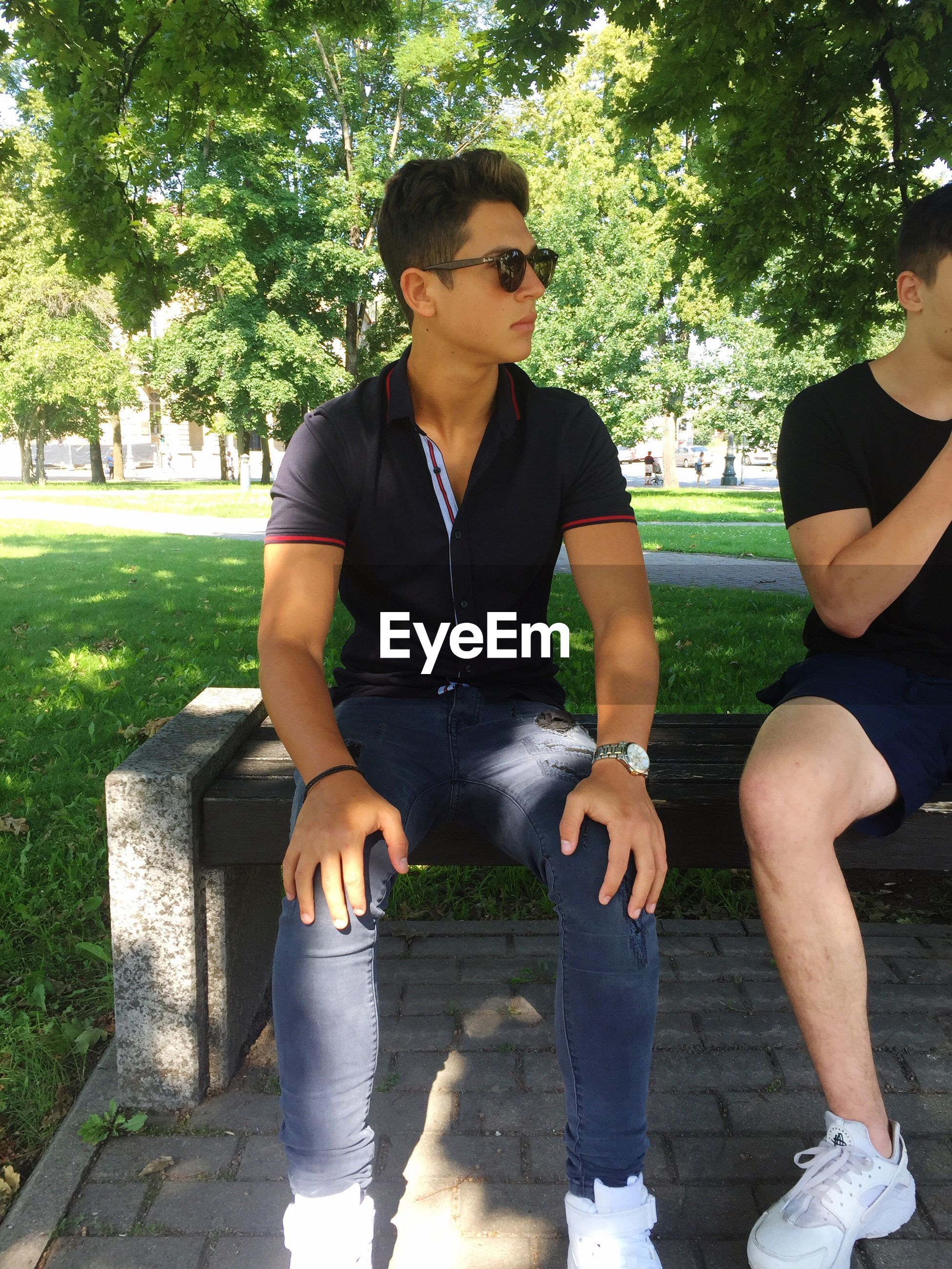 real people, casual clothing, sitting, young men, young adult, two people, leisure activity, day, outdoors, young women, tree, lifestyles, full length, togetherness, front view, park - man made space, growth, grass, nature