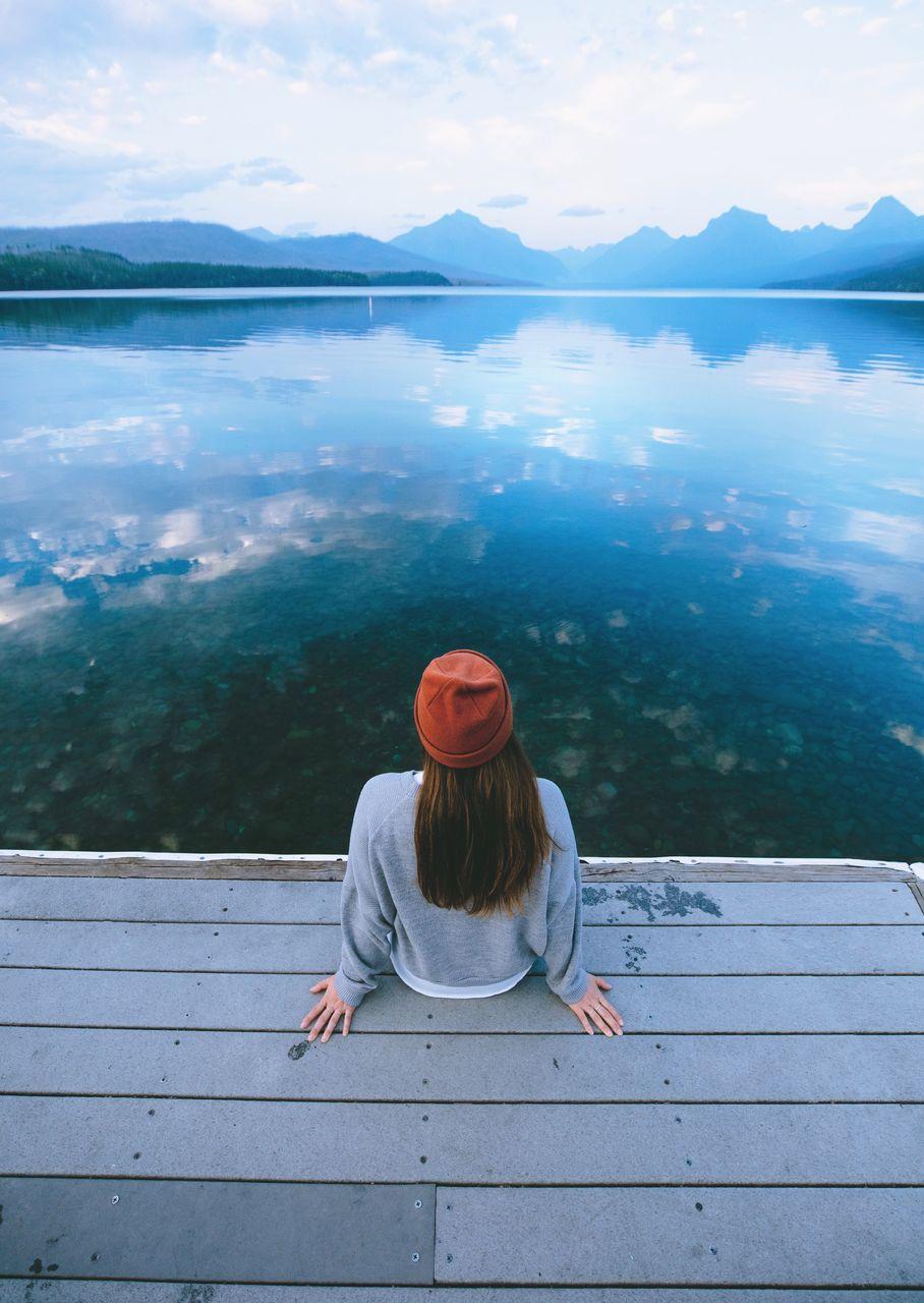 Woman Sitting On Pier By Lake
