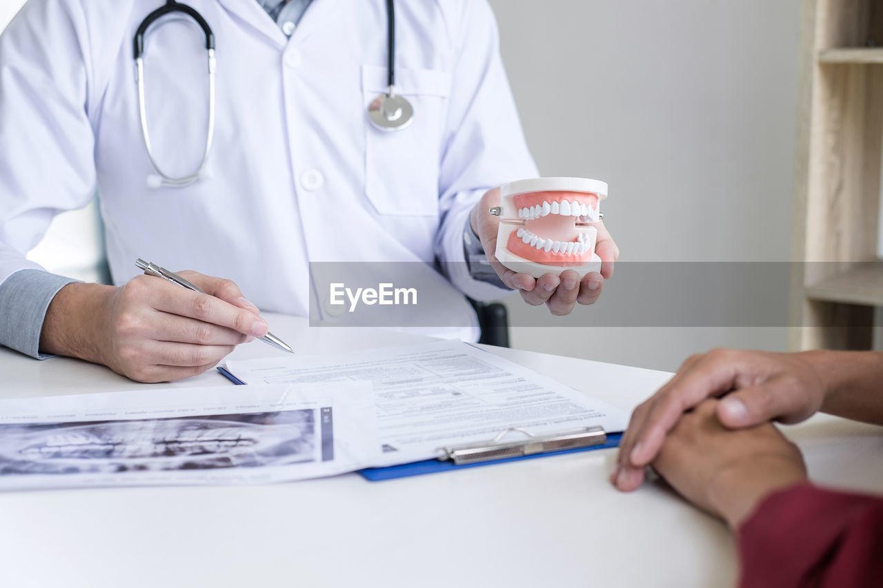 occupation, midsection, doctor, indoors, hand, human hand, holding, real people, healthcare and medicine, table, two people, people, professional occupation, front view, men, lab coat, medical occupation, expertise, medical supplies, clothing, healthcare worker, care, responsibility