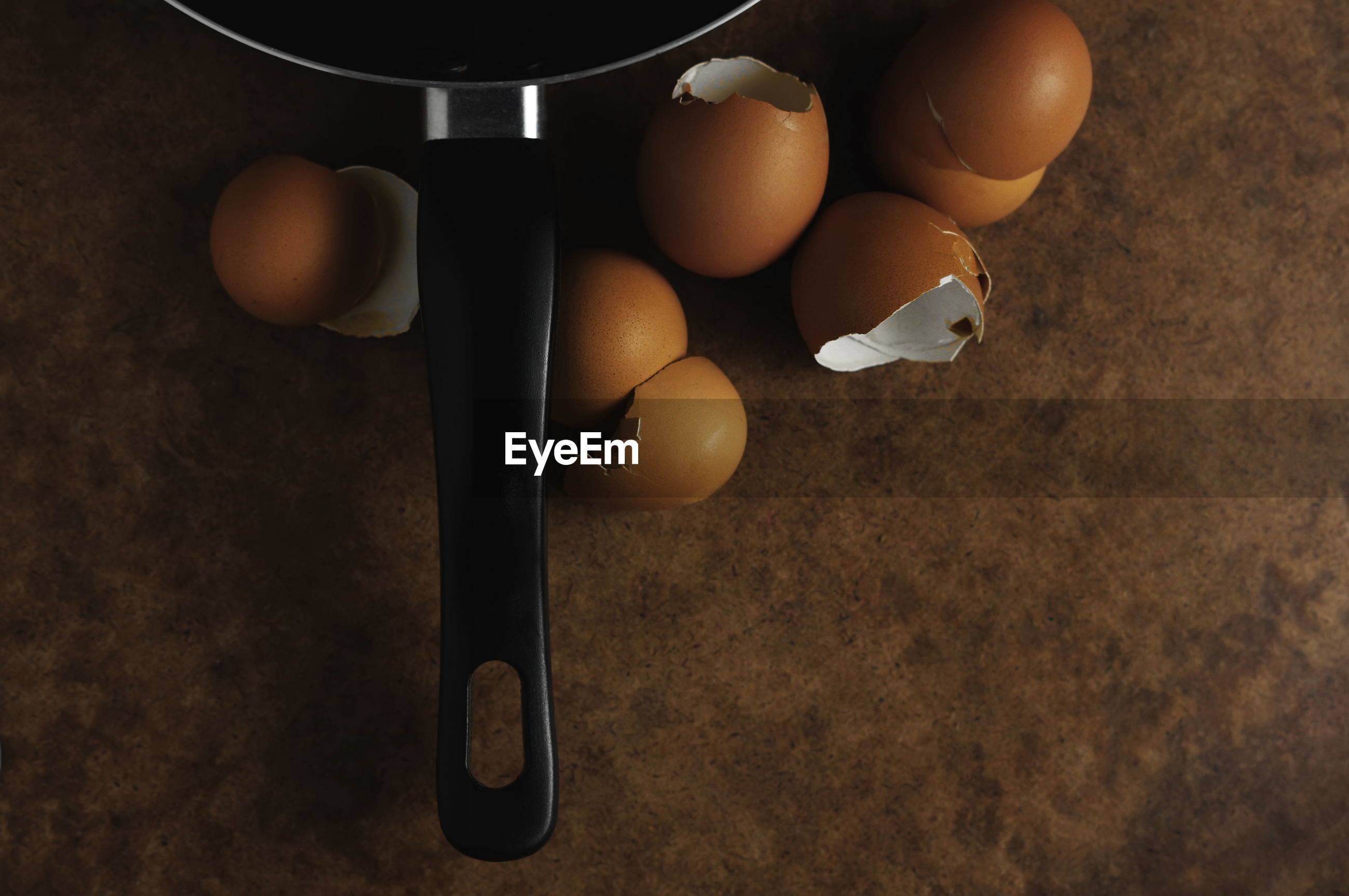High angle view of cooking pan with eggshells in kitchen on wooden table