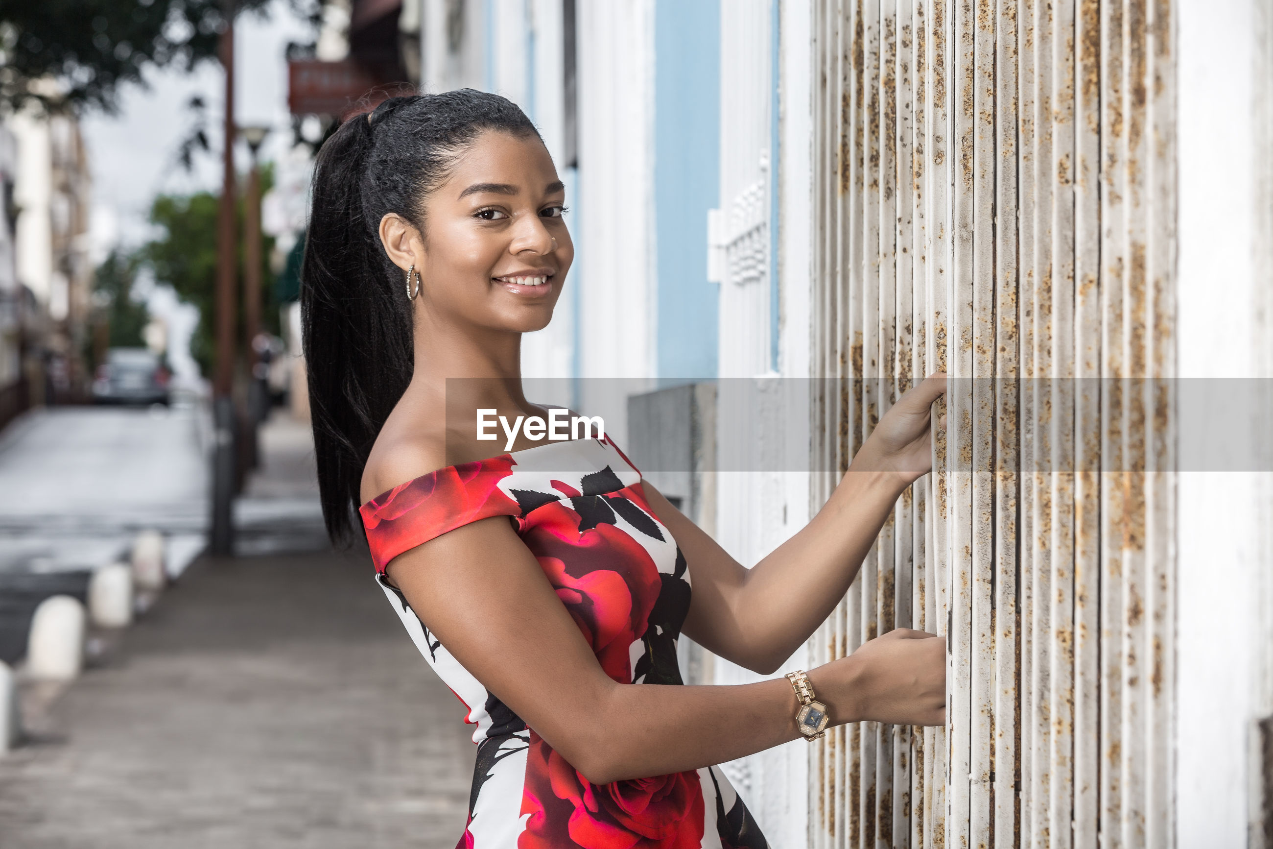 Portrait of smiling young woman standing on sidewalk