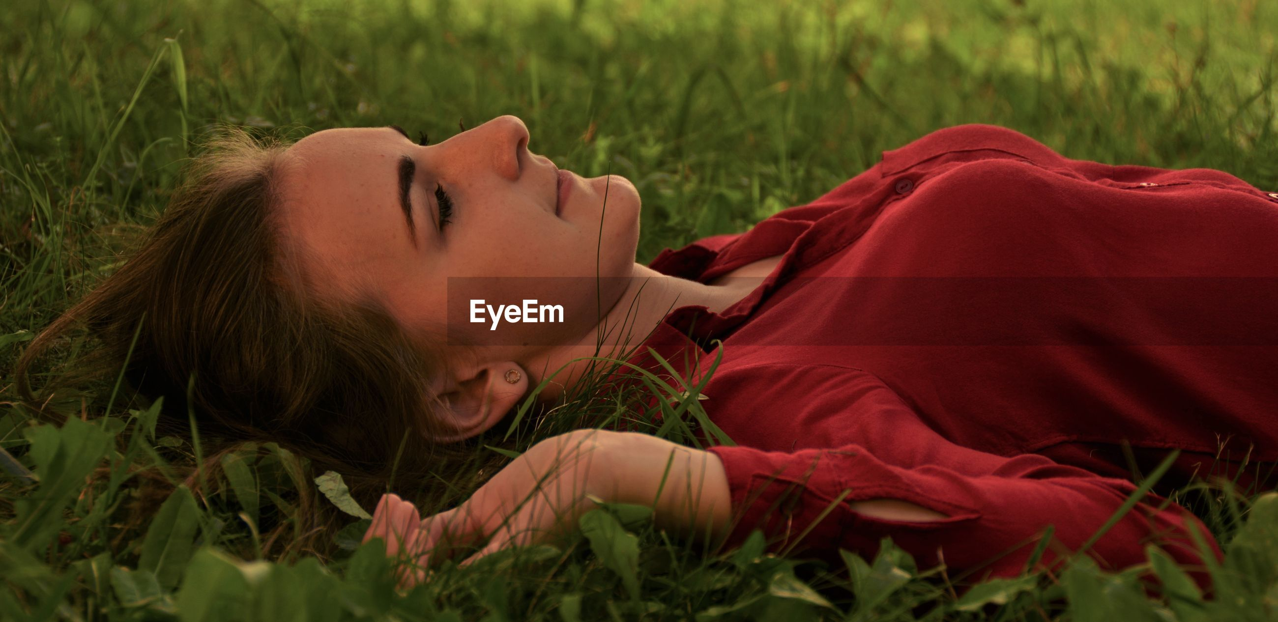 Close-up of woman lying on grass in park