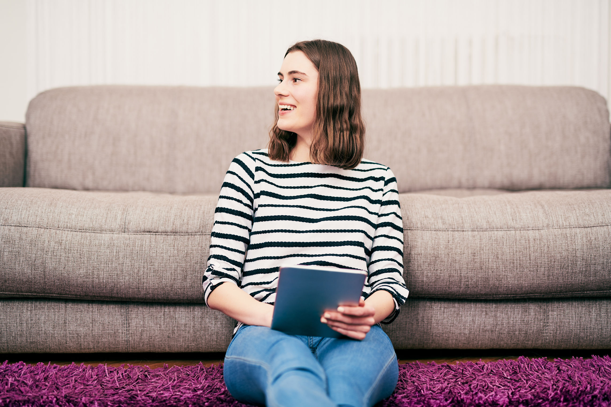 Smiling woman using digital tablet while sitting at home
