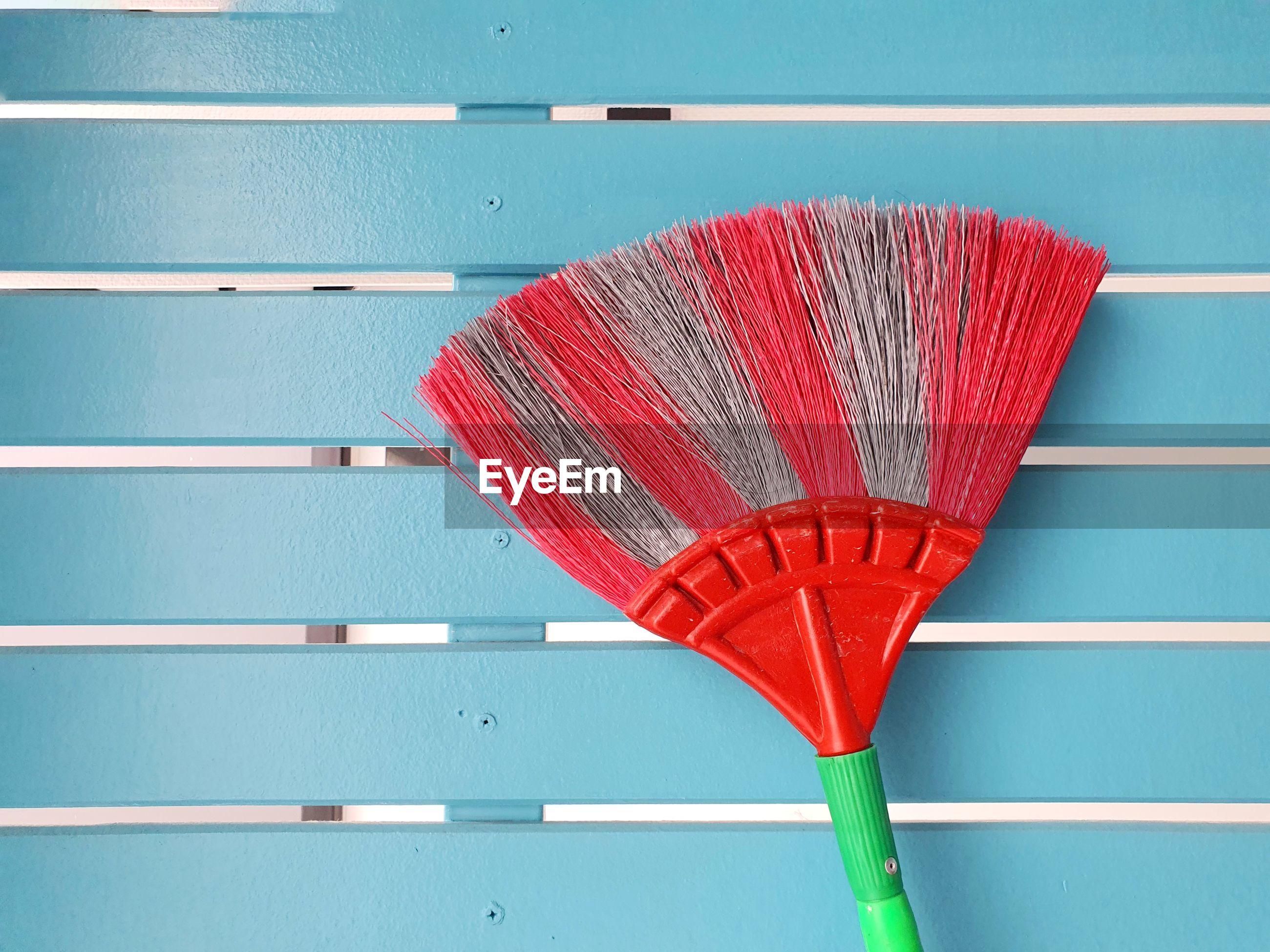 Cobweb broom on blue wall. household equipment concept