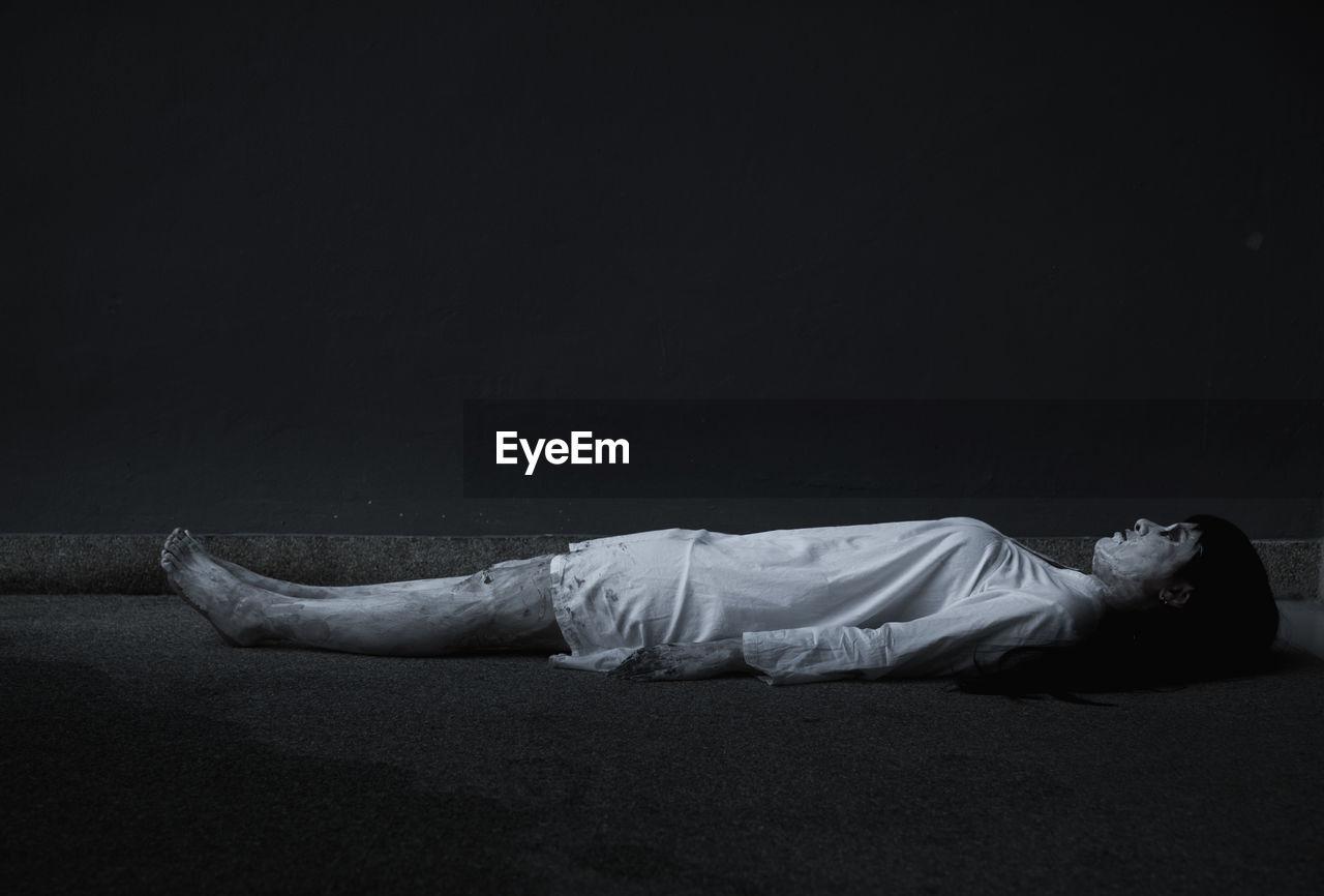 Side view of man sleeping against black background