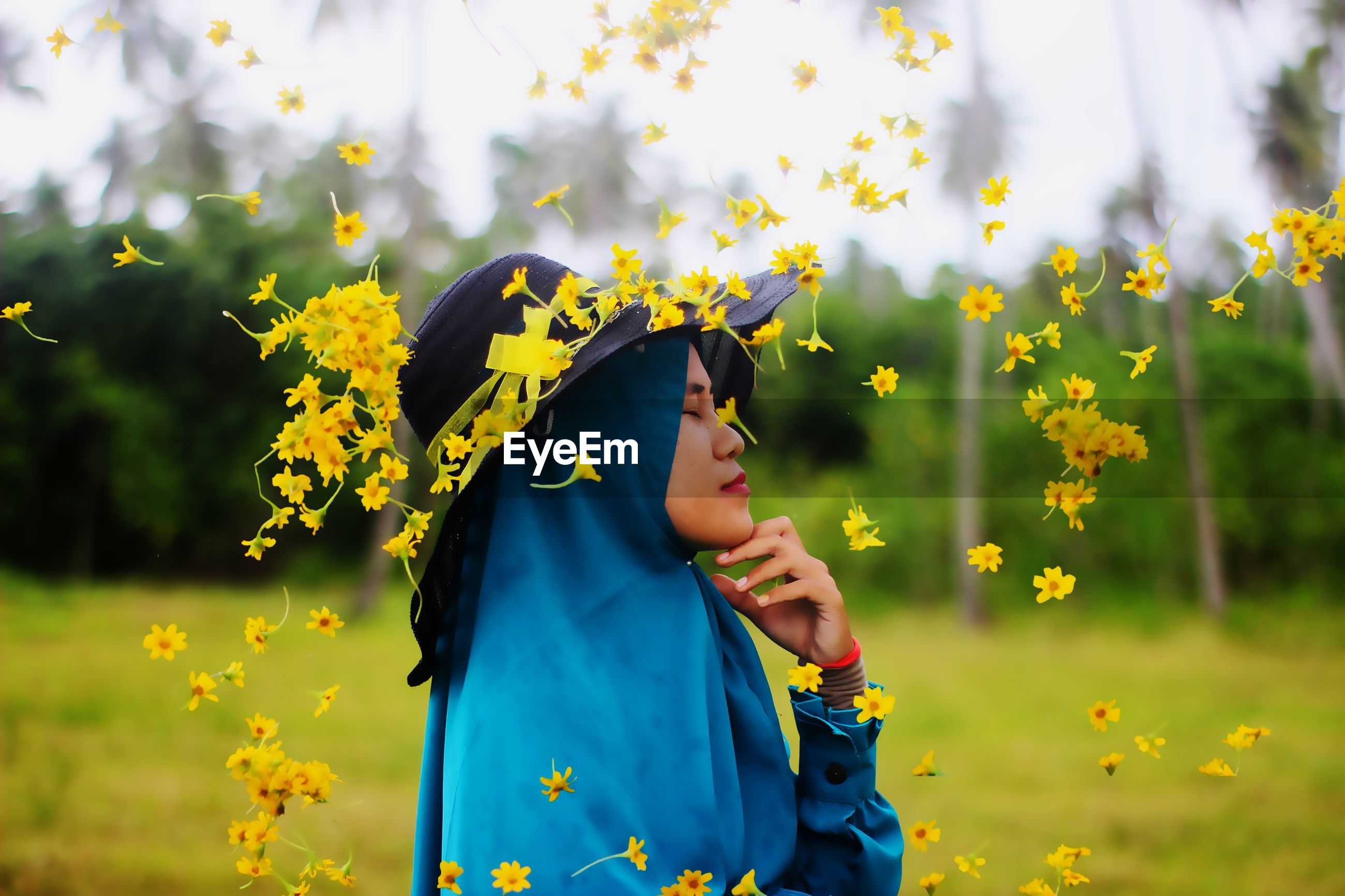 Woman standing on yellow flowering plants on field