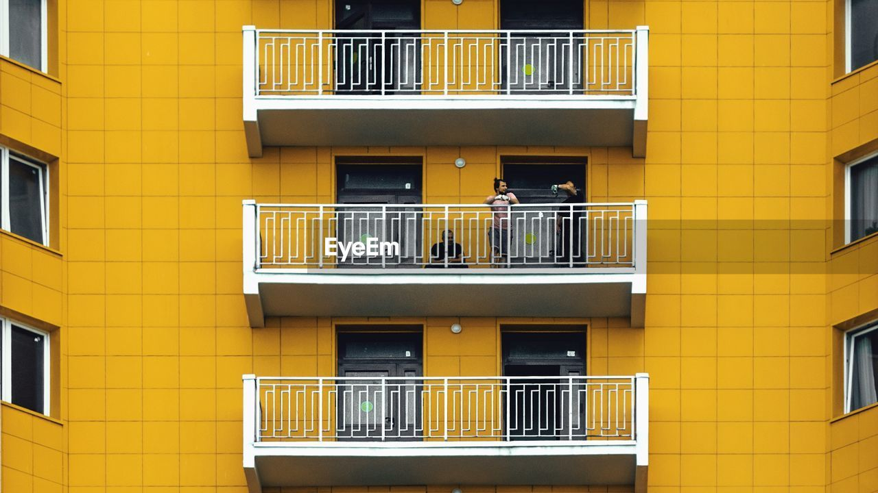 window, building exterior, balcony, architecture, built structure, railing, outdoors, no people, residential building, day, yellow