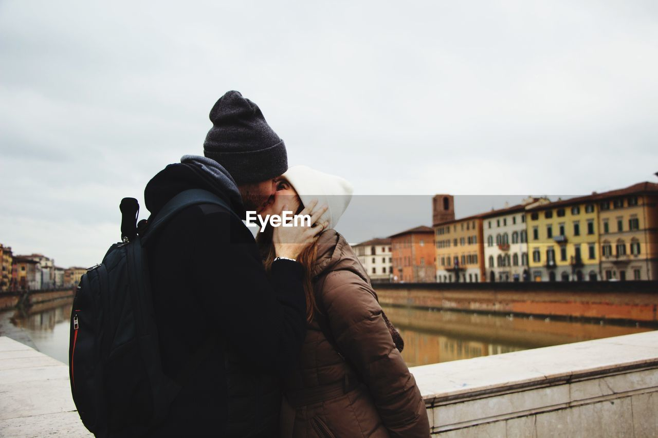 Couple Kissing While Standing By Canal Against Sky In City