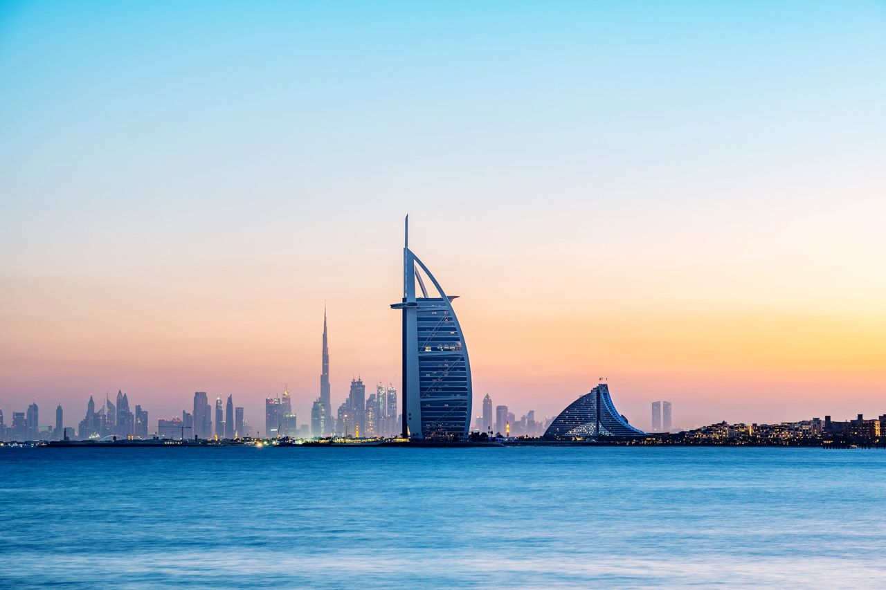 sky, building exterior, architecture, built structure, building, city, waterfront, sunset, water, skyscraper, office building exterior, urban skyline, no people, landscape, travel destinations, tall - high, sea, nature, tower, cityscape, outdoors, financial district