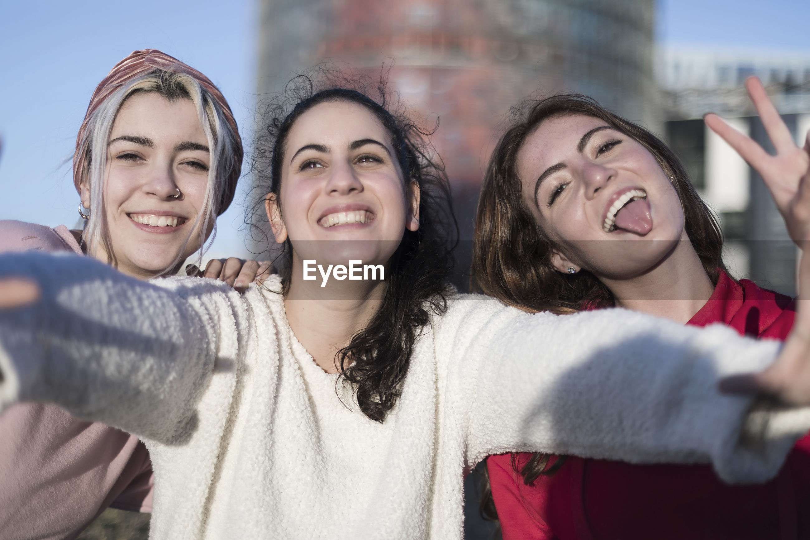 Portrait of smiling young woman with friends against building