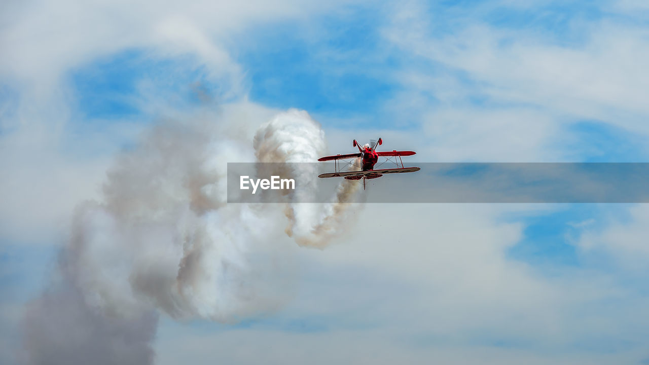 air vehicle, cloud - sky, airplane, flying, mode of transportation, airshow, transportation, smoke - physical structure, sky, on the move, motion, low angle view, fighter plane, plane, mid-air, travel, day, nature, teamwork, speed, no people, aerobatics, outdoors, vapor trail, aerospace industry