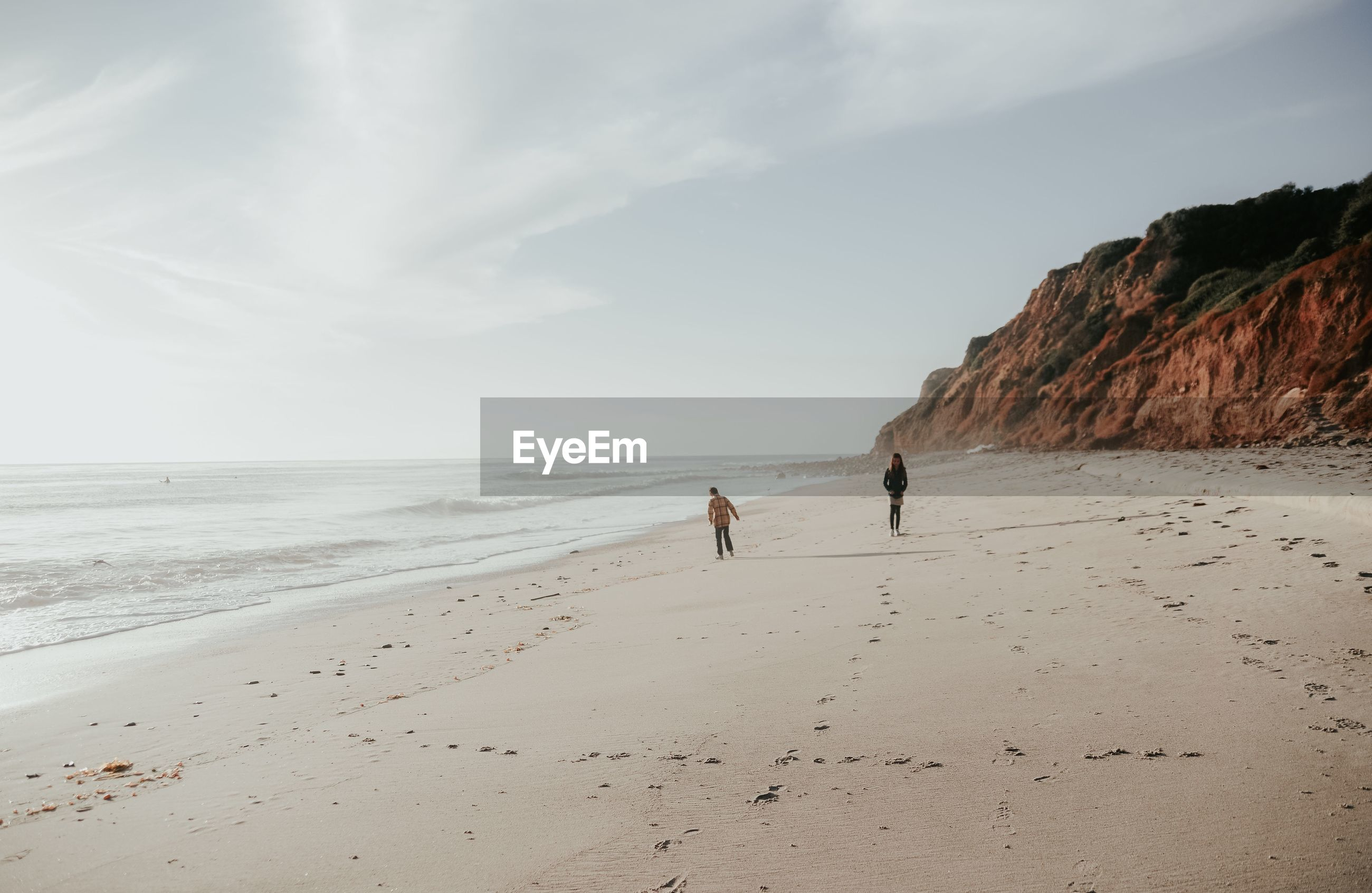 Siblings walking at beach against sky during sunny day