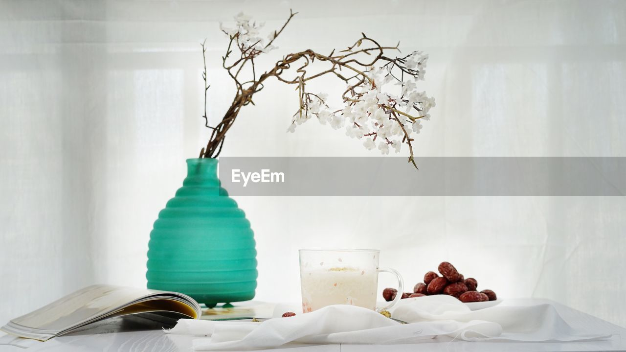 Food and drink by white flowers on table at home