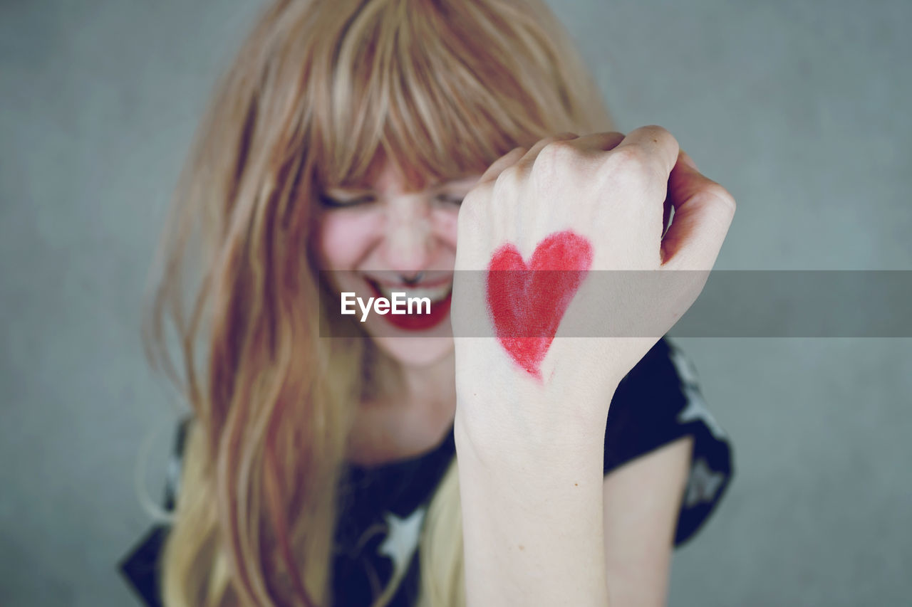 Happy young woman with heart shape on hand against gray background