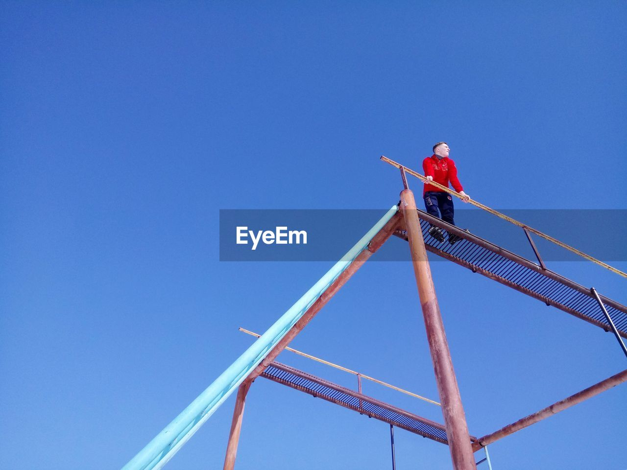sky, blue, low angle view, copy space, clear sky, men, construction industry, nature, one person, day, industry, architecture, built structure, real people, occupation, construction site, metal, outdoors, working