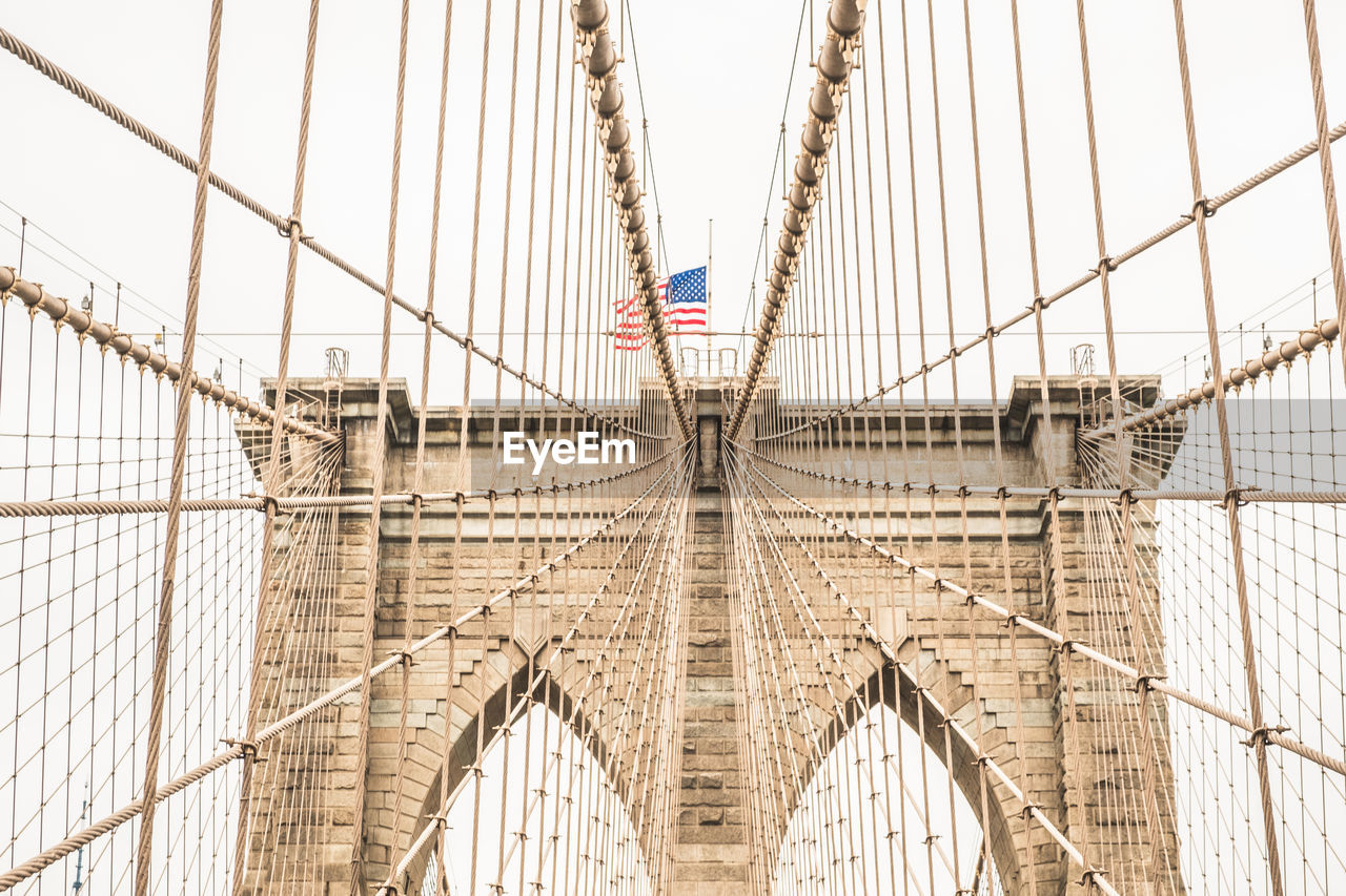 patriotism, flag, bridge - man made structure, suspension bridge, connection, built structure, architecture, national icon, day, no people, pride, transportation, bridge, stars and stripes, outdoors, sky, city