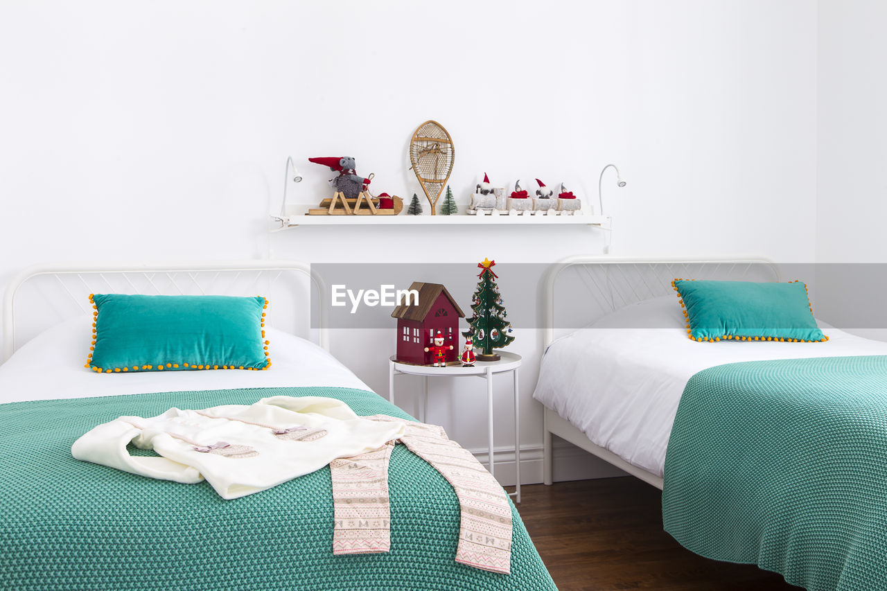 indoors, furniture, no people, table, pillow, still life, bed, home interior, domestic room, absence, cushion, textile, decoration, stuffed, wall - building feature, home, green color, home showcase interior, arrangement, representation, tray