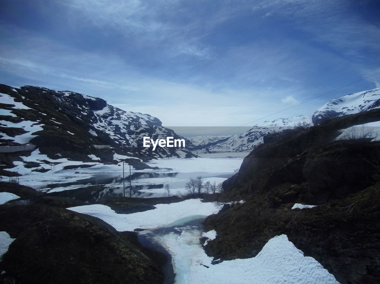 winter, cold temperature, beauty in nature, water, scenics - nature, tranquil scene, tranquility, sky, mountain, snow, cloud - sky, environment, no people, nature, mountain range, day, rock, non-urban scene, snowcapped mountain, outdoors