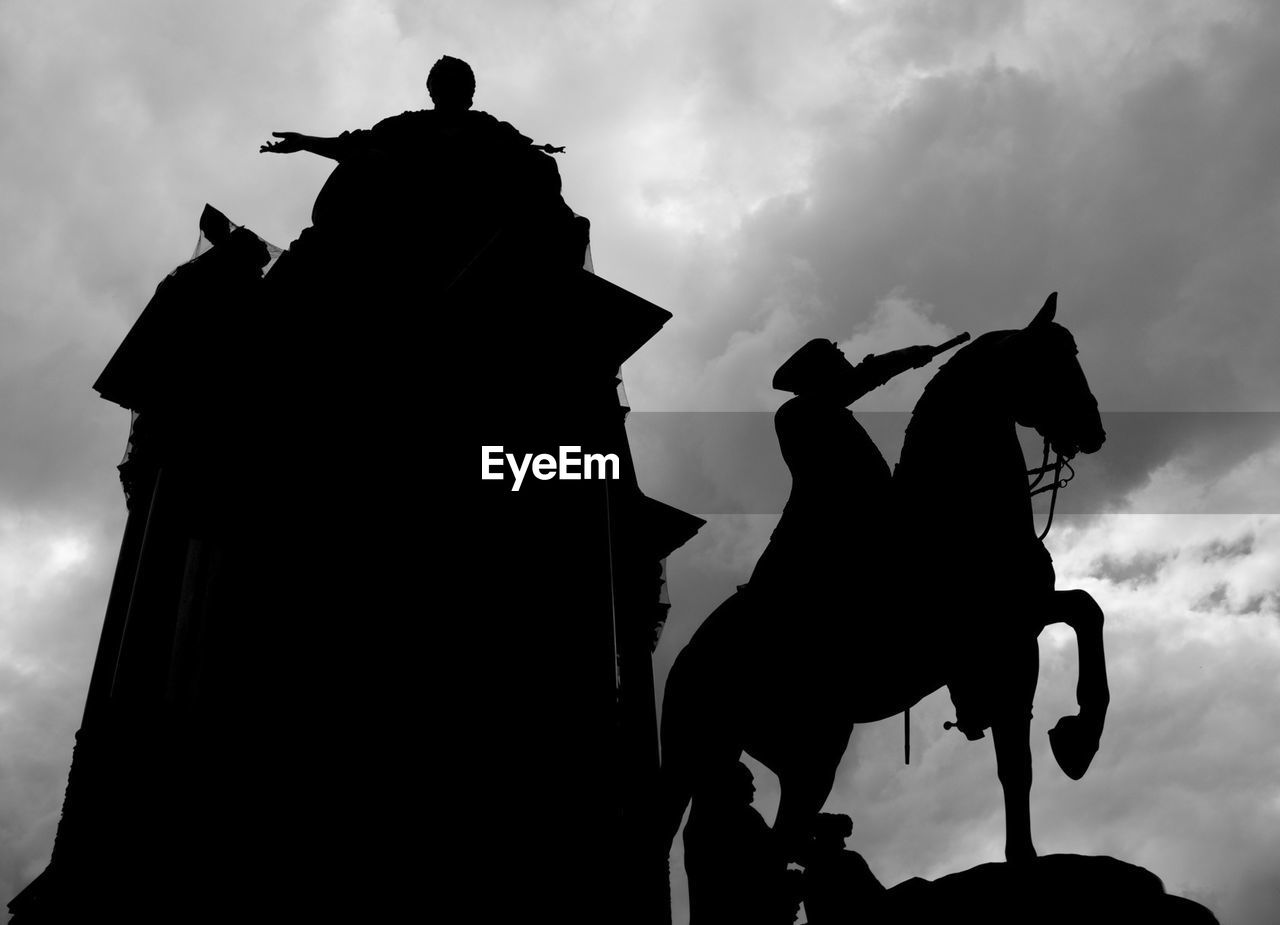 horse, silhouette, horseback riding, sky, cloud - sky, low angle view, statue, sculpture, riding, outdoors, jockey, day, real people, animal themes, mammal, people