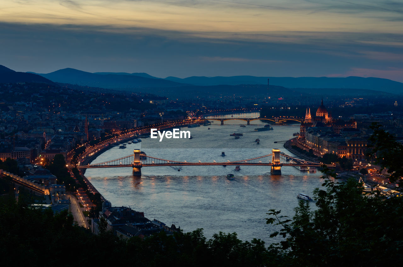 architecture, built structure, connection, bridge - man made structure, sky, building exterior, mountain, river, travel destinations, water, cloud - sky, suspension bridge, city, chain bridge, outdoors, high angle view, cityscape, transportation, sunset, travel, tree, no people, illuminated, nature, day, beauty in nature