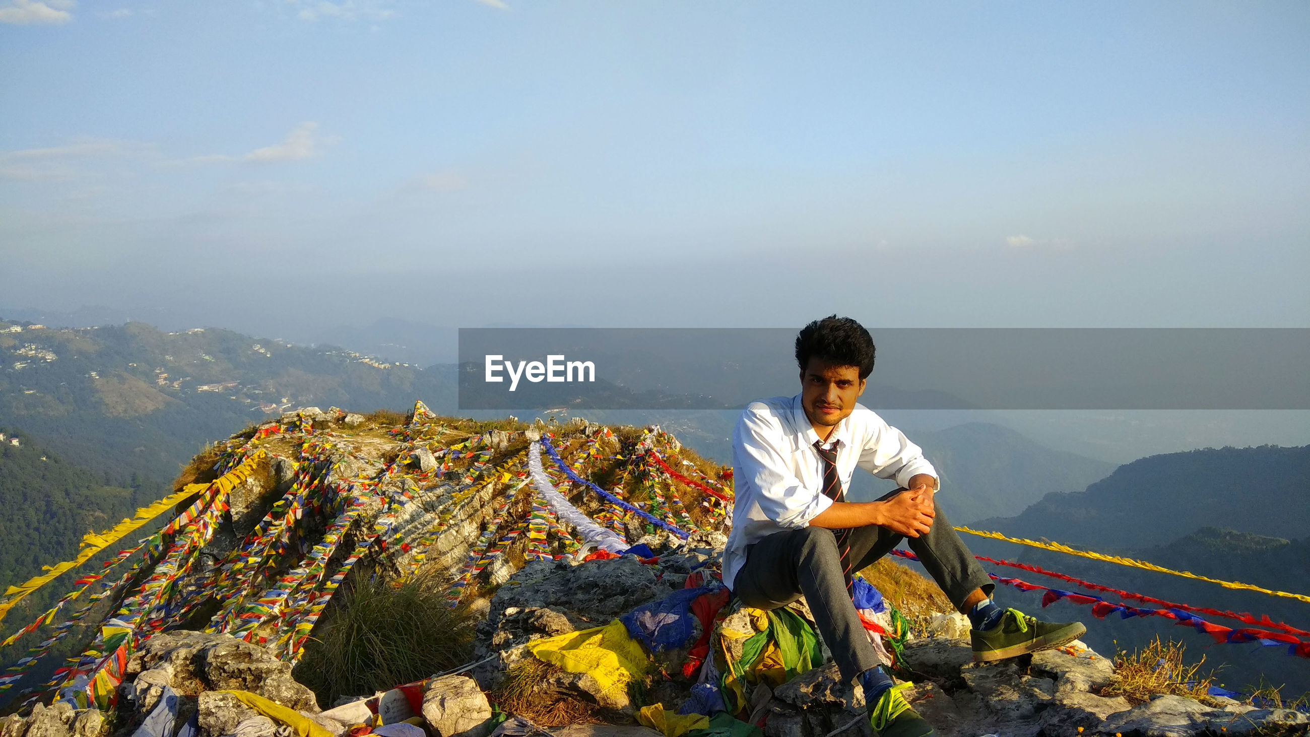Young man sitting on mountain with prayer flags against sky