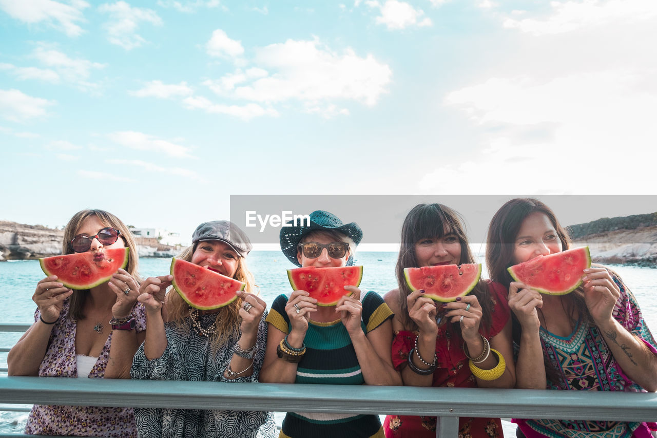 Friends holding watermelon slices against sea and sky