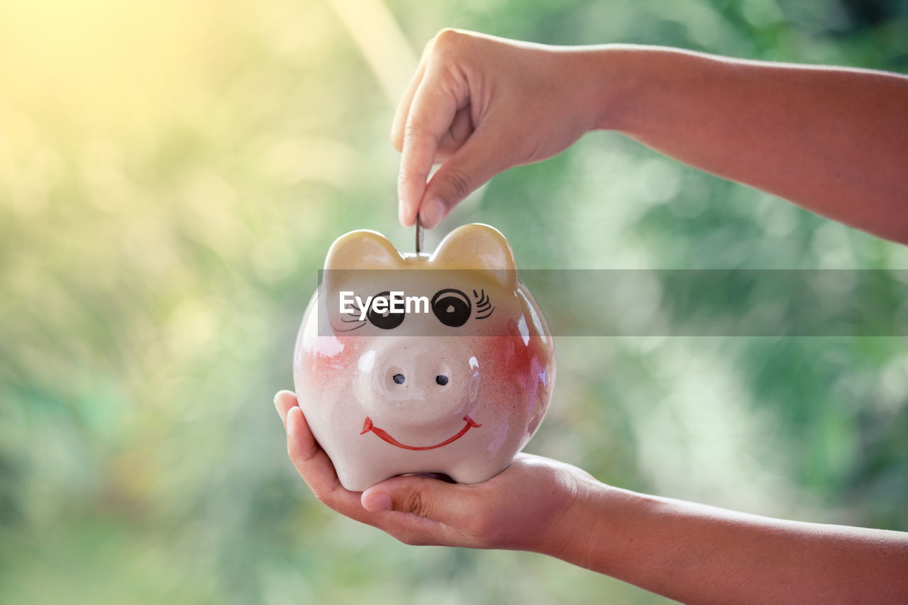 Cropped Hand Of Woman Putting Coin In Piggy Bank