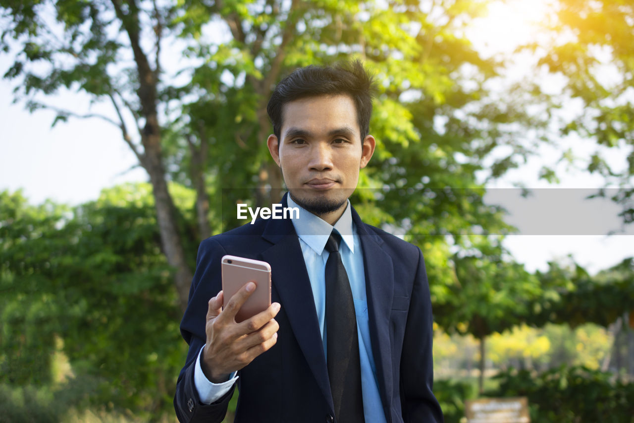 one person, business person, businessman, business, wireless technology, suit, technology, real people, looking at camera, focus on foreground, portrait, standing, well-dressed, waist up, young adult, corporate business, males, young men, front view, men, outdoors